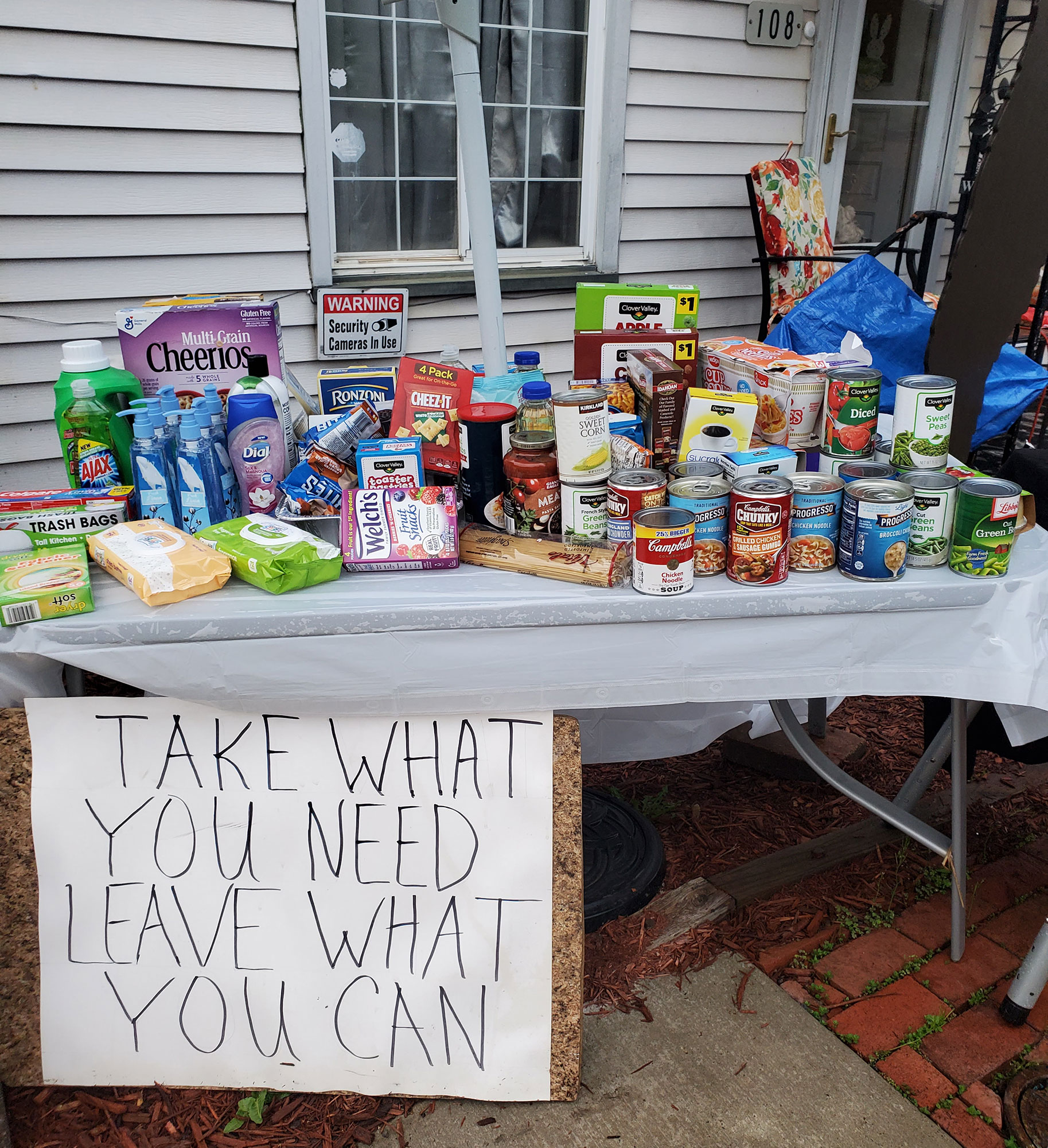 "A table filled with food donations at Virginia's house encourages visitors to ""Take What You Need, Leave What You Can."""