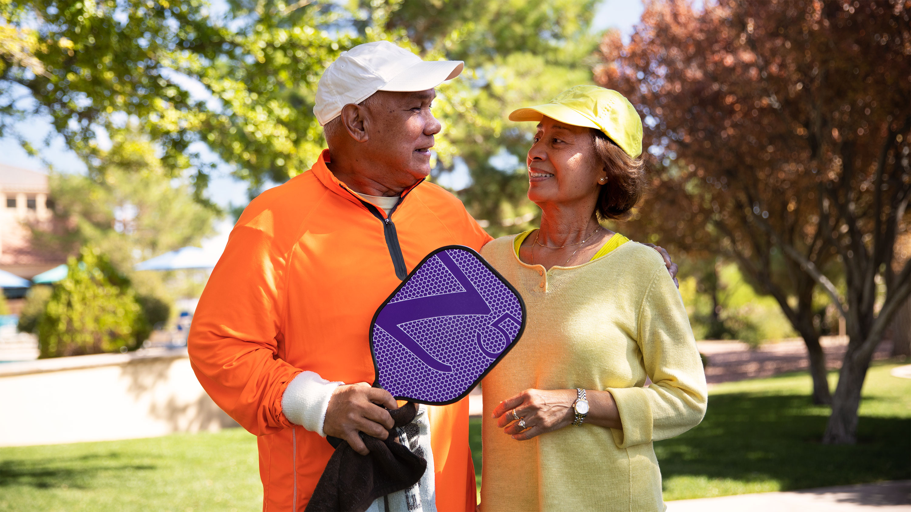 A mature male and female couple, dressed in brightly-colored athletic clothing, play paddleball outdoor on an autumn days.