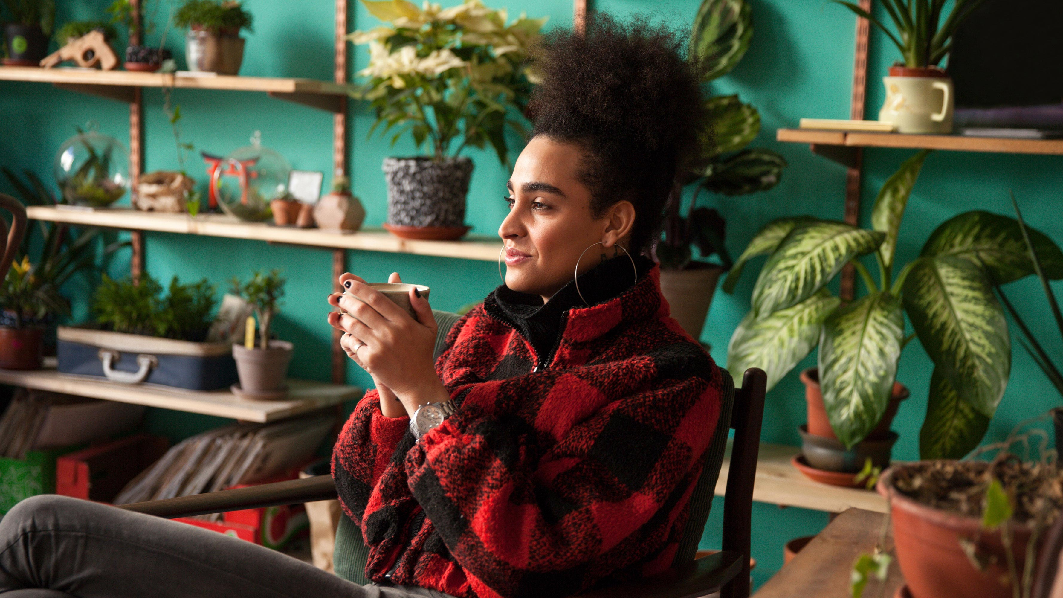 A woman, wearing a red and black sweater, holds a cup of tea with both hands while relaxing in her plant-filled living room.
