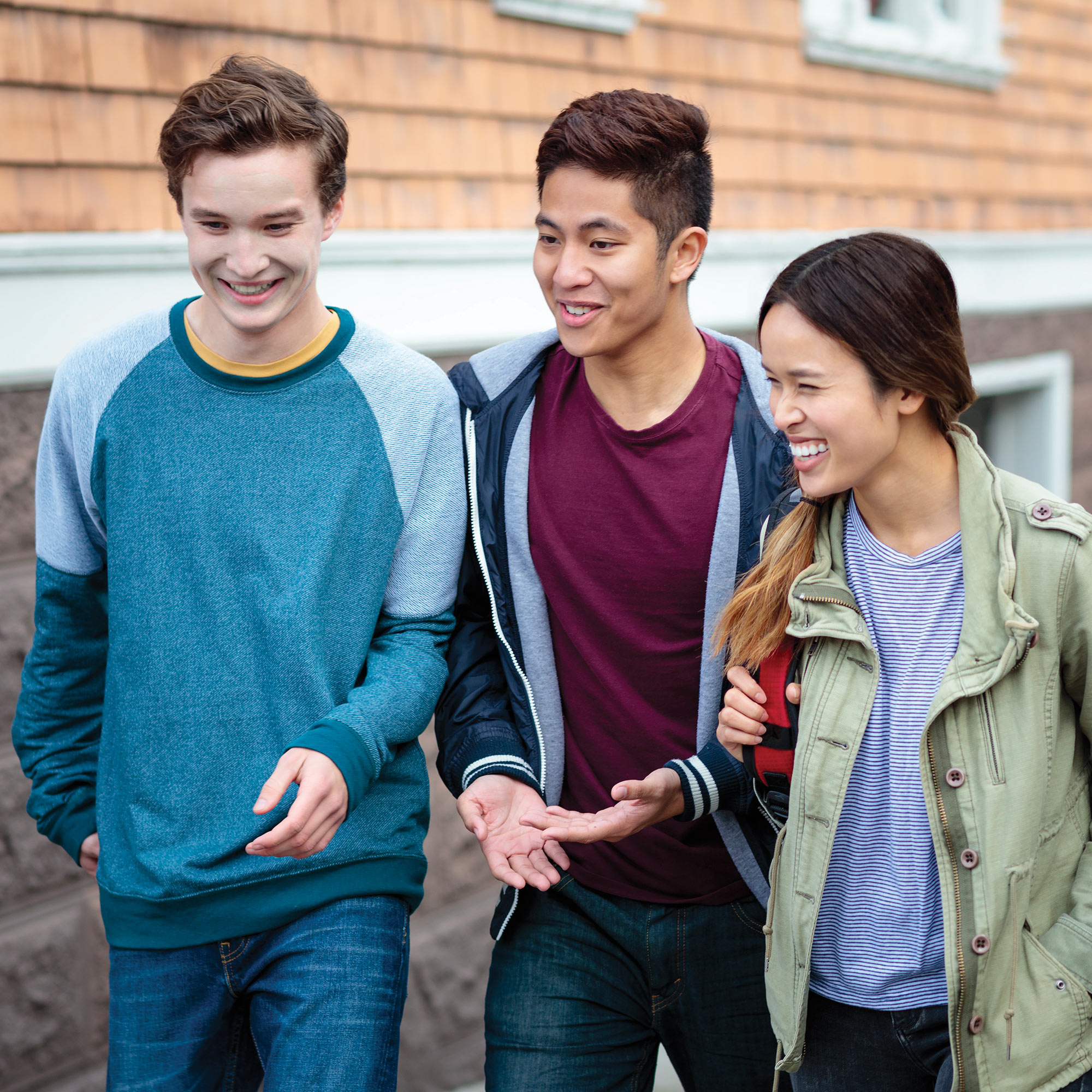A group of young adults walking down a city sidewalk, talking and smiling.