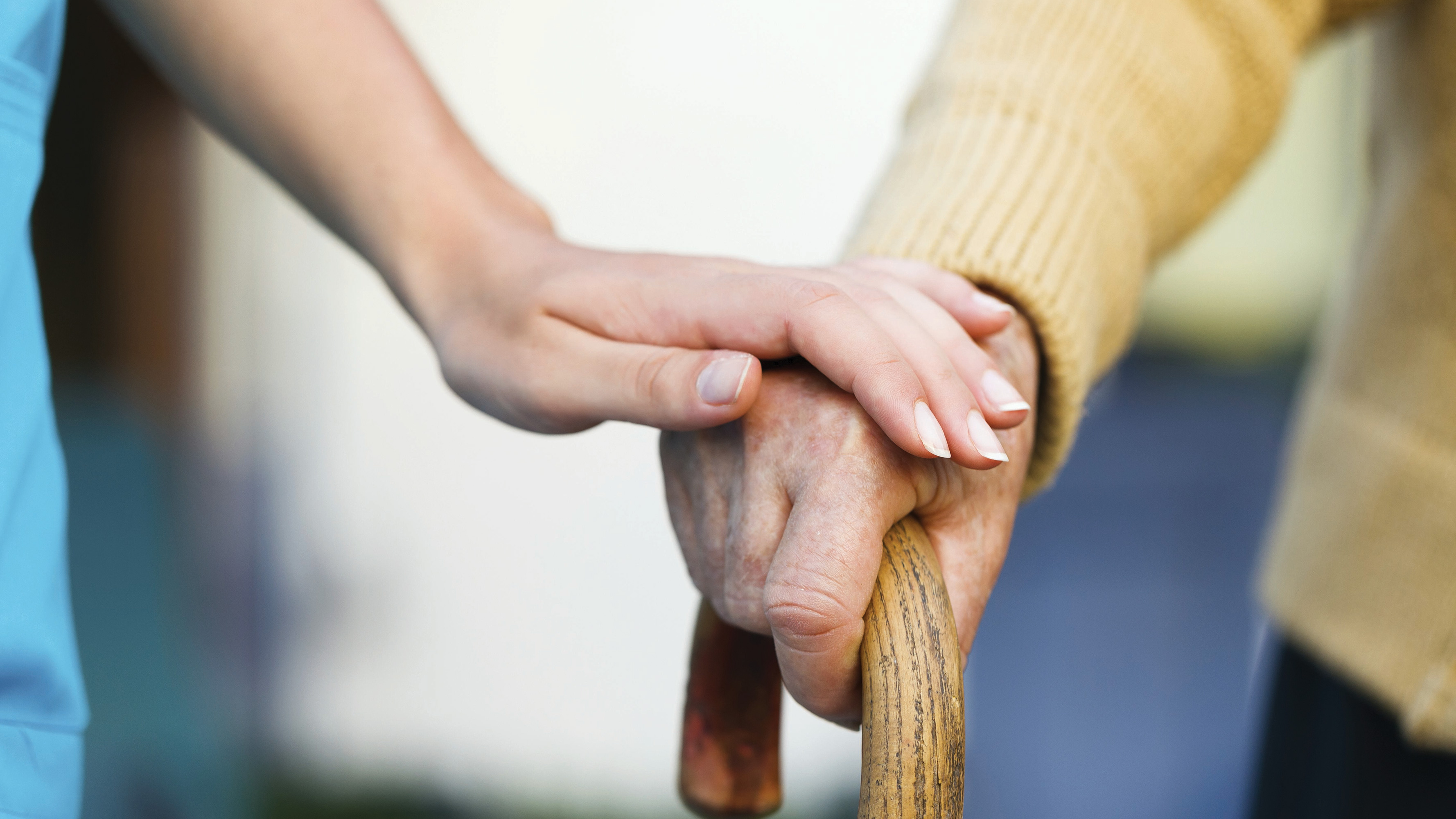 An elderly person's hand on a cane with a caregiver's hand on top in a reassuring gesture.