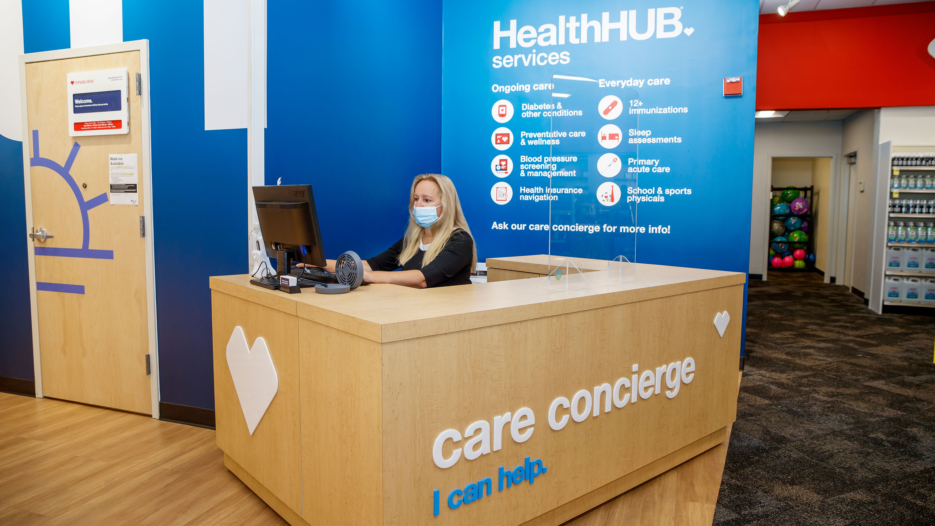 A masked Care concierge uses the computer at the check-in station for a HealthHUB inside a CVS MinuteClinic