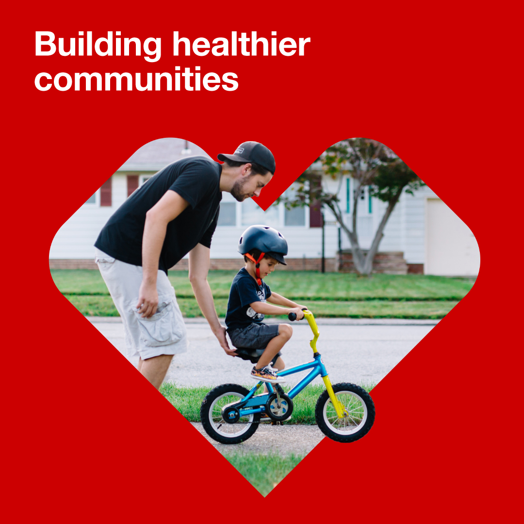 Building healthier communities | Dad helping child on bike inside heart logo.