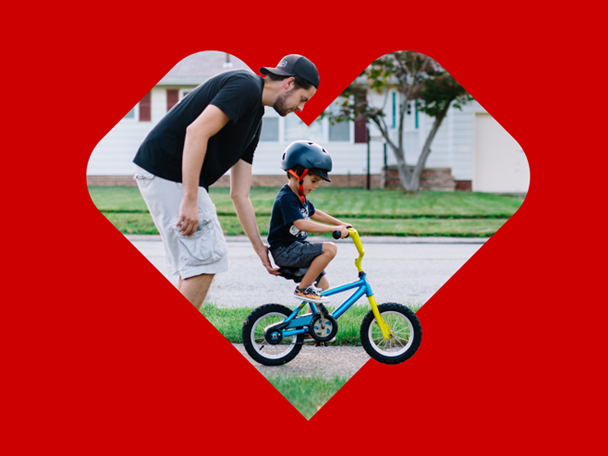 Dad helping child on bike inside heart logo.