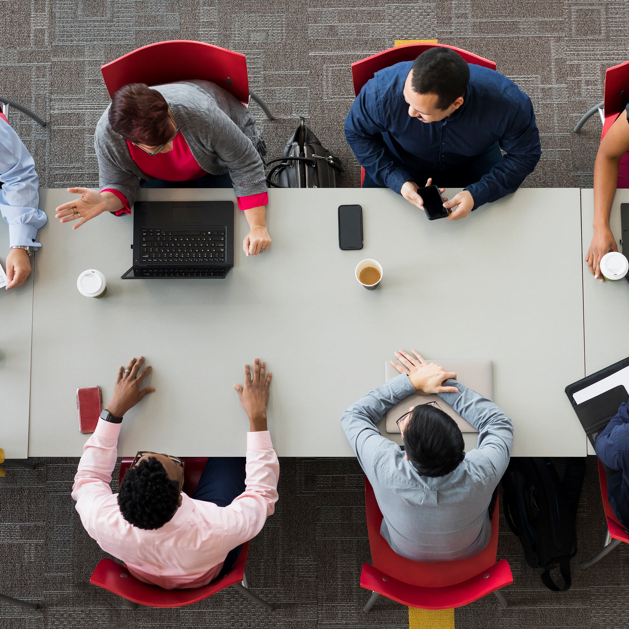 An overhead view of several different CVS Health colleagues, gathered around a conference table, using laptops and taking notes, as part of a team meeting.