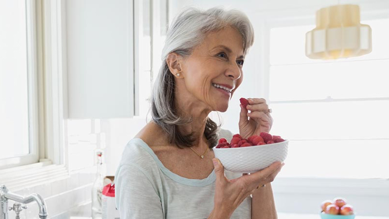 A smiling woman stands near her sink with a bowl of raspberries in hand.