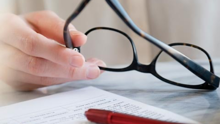 A hand holds the temple of a pair of black glasses over a tabletop filled with papers.