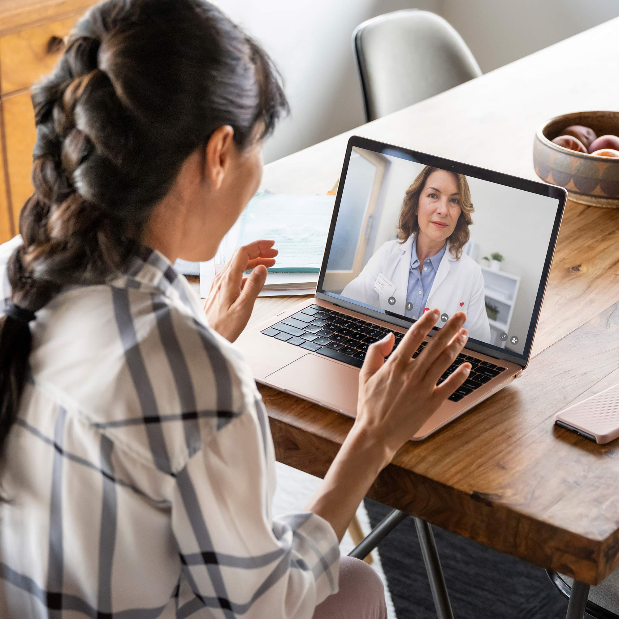 A woman seated at her dining room table video chats with her doctor on her laptop.