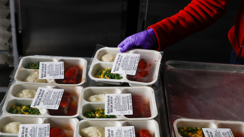 A volunteer arranges pre-packaged cooked meals, in sealed containers, on a tray for distribution.