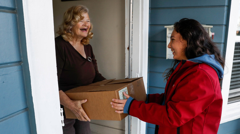 A female volunteer, wearing a red coat, delivers a box containing food donations to female senior citizens, who is smiling while standing in the doorway of her house.