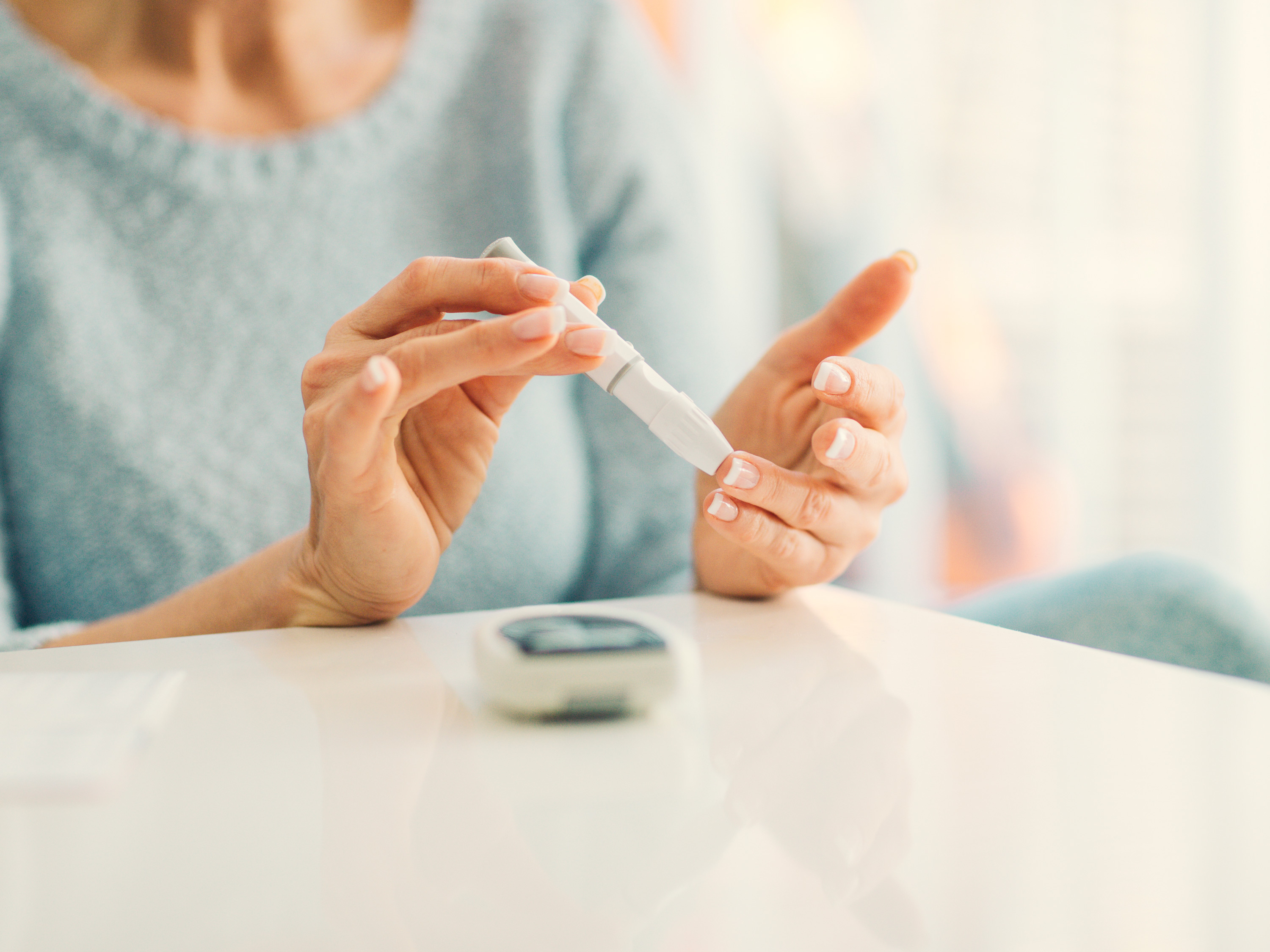 A photo of a woman testing blood sugar with finger prick.
