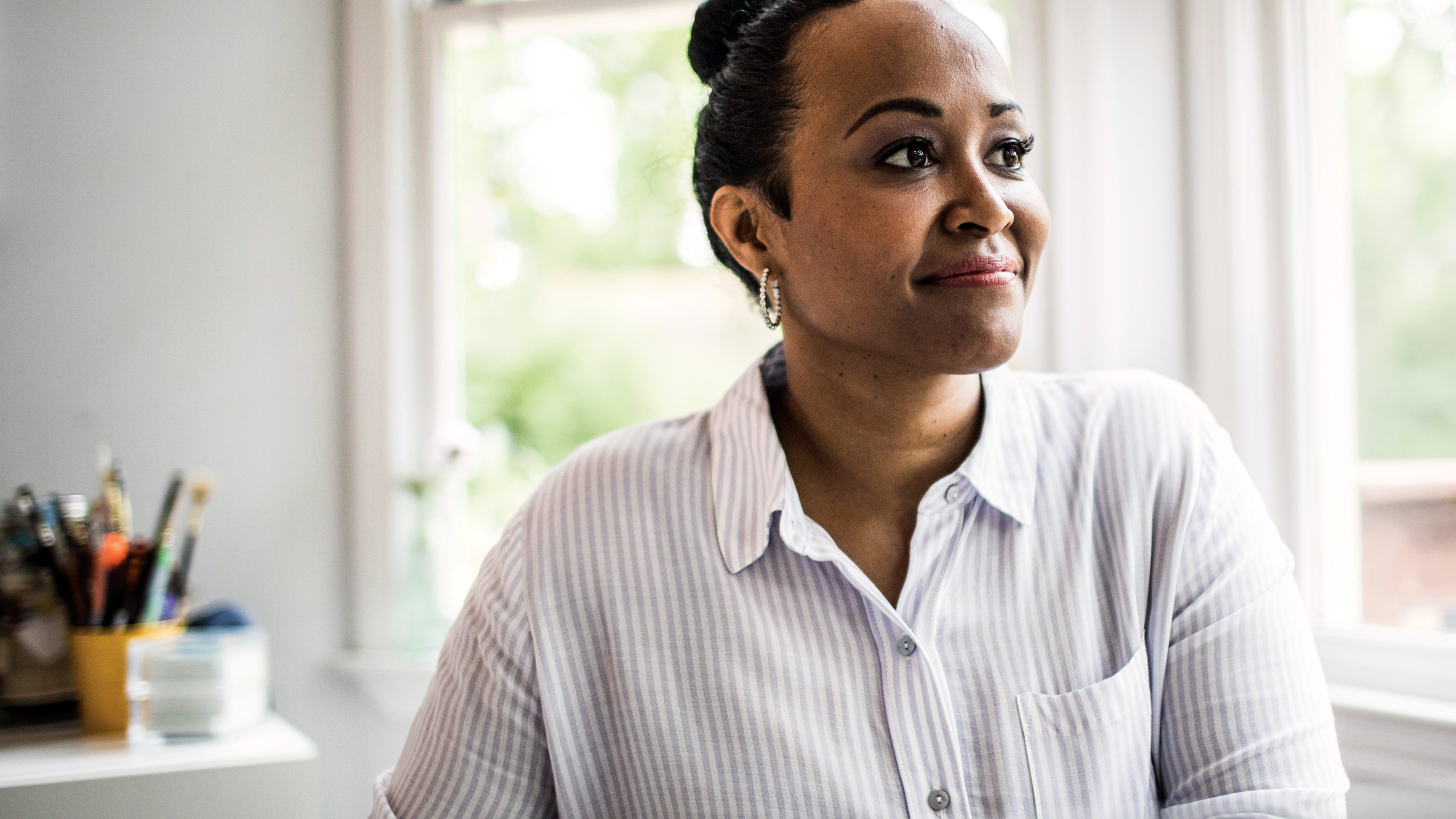 An African-American woman gazes out of a window in her modern home office, smiling.