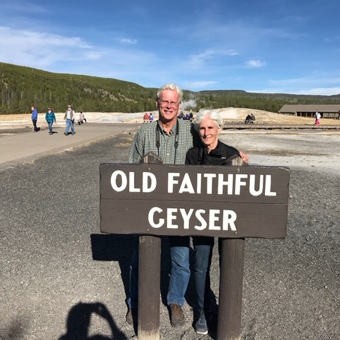 "Katie standing with her husband by a sign that reads, ""Old Faithful Geyser"""