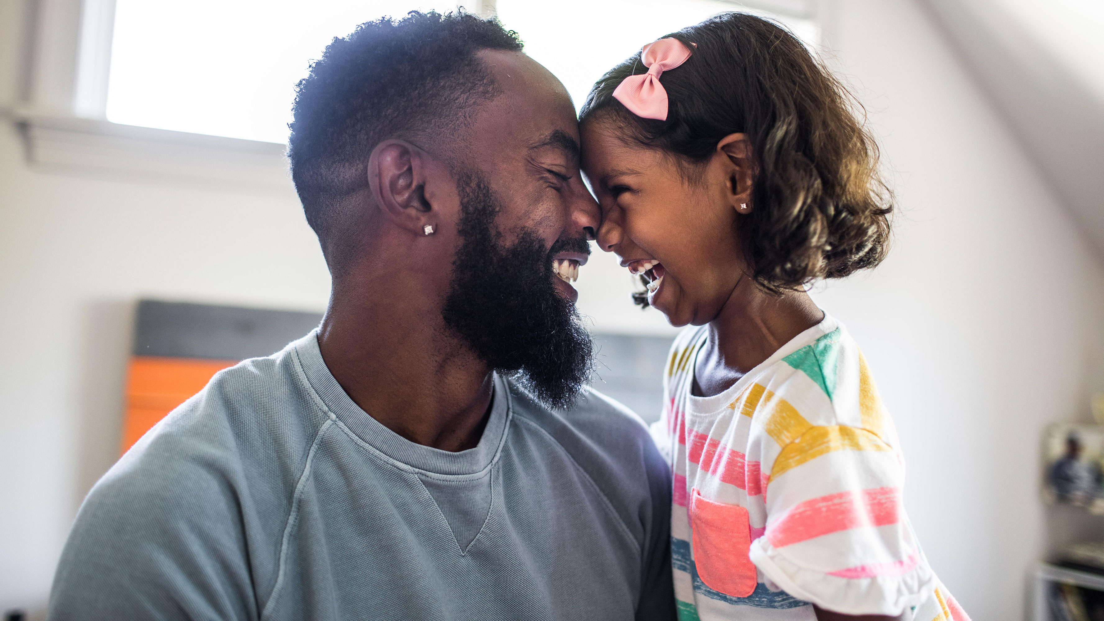 A father and daughter share in a smiling moment in a modern-looking living room.