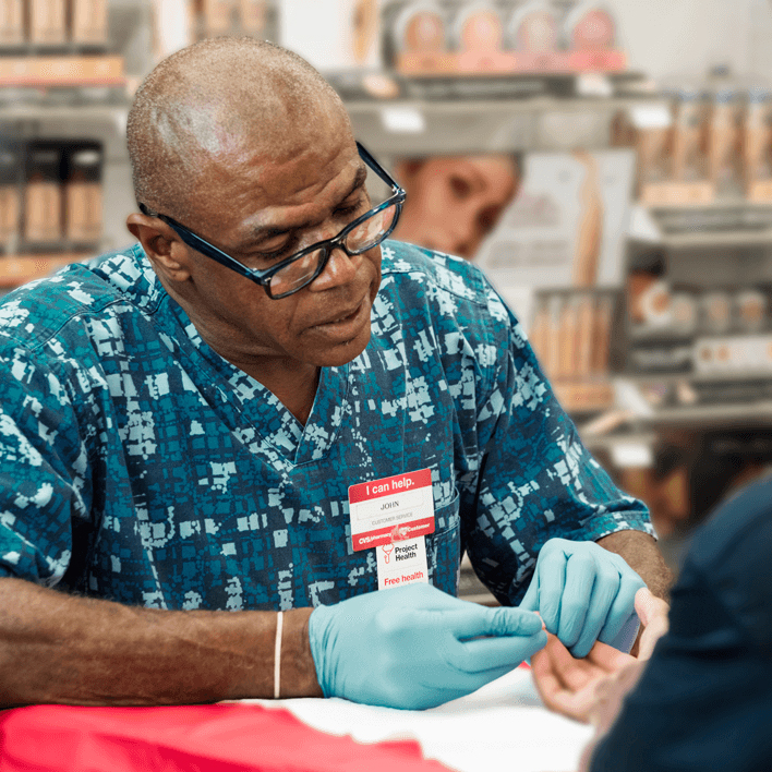 A CVS Pharmacy associate runs complimentary diagnostic test for an unknown participant in the Project Health program.