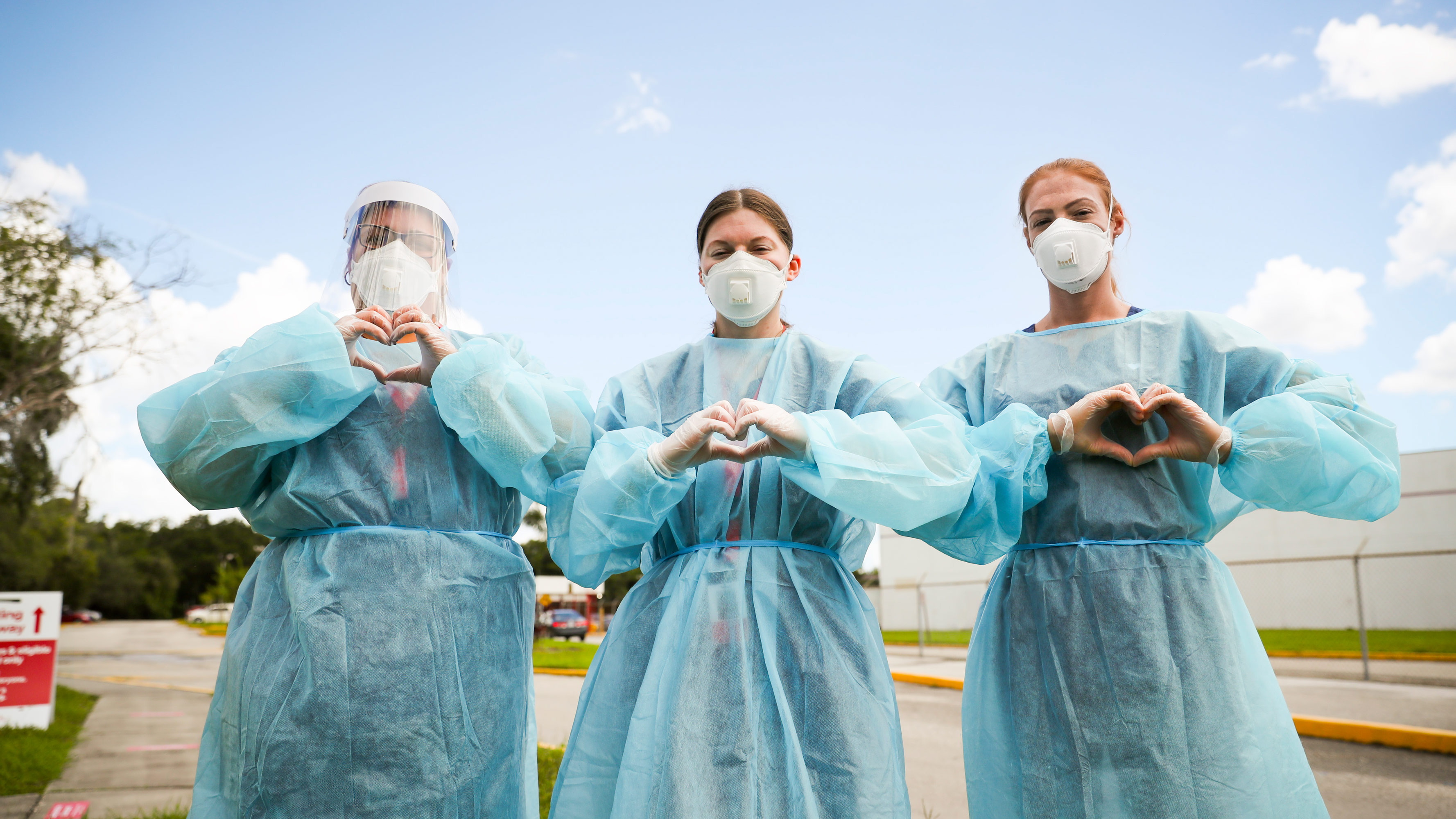 Three nurses hold their hands up in heart shapes near a COVID-19 testing station.