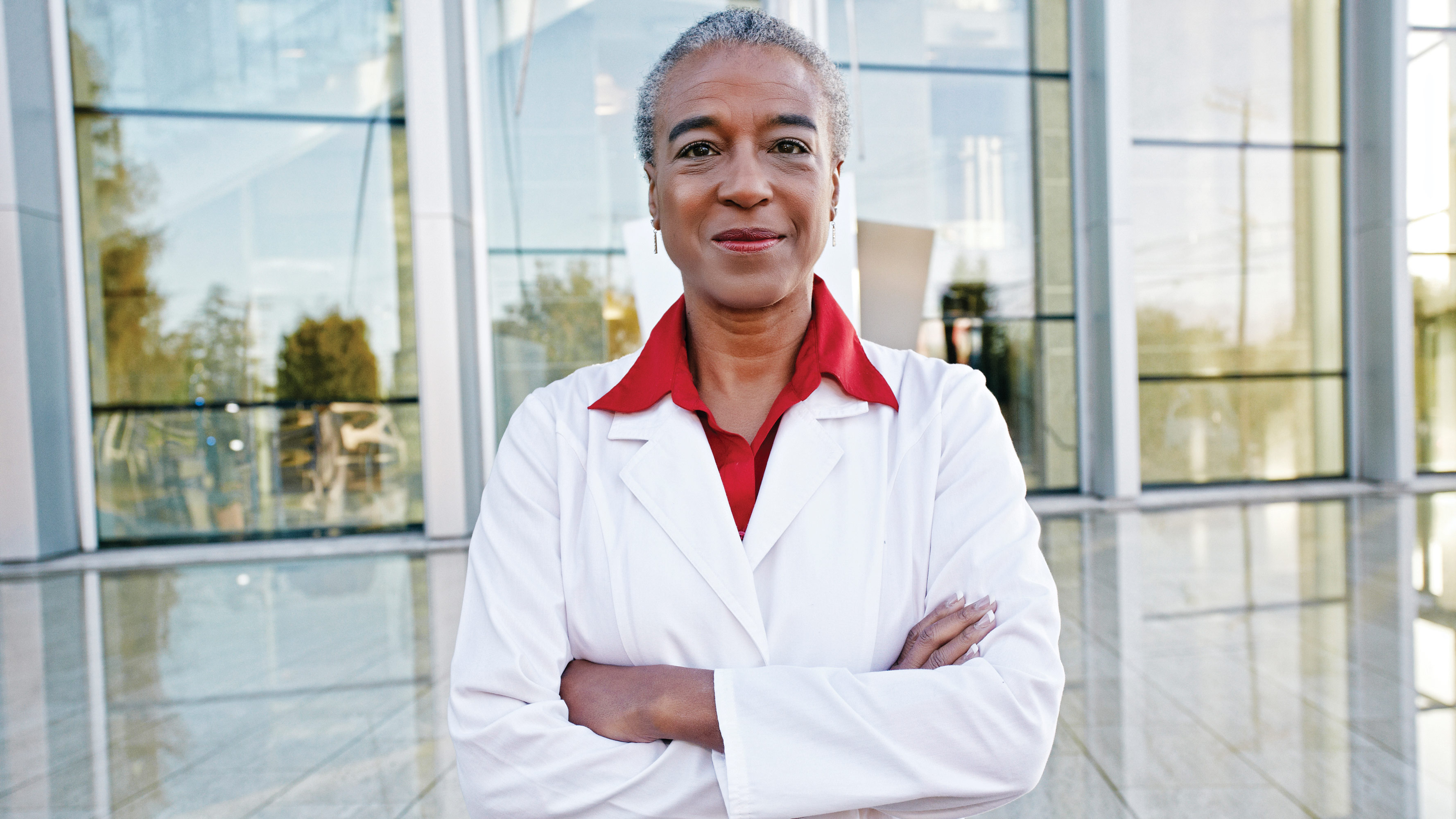 A smiling doctor in a lab coat and red shirt stands in front of a building with her arms crossed.