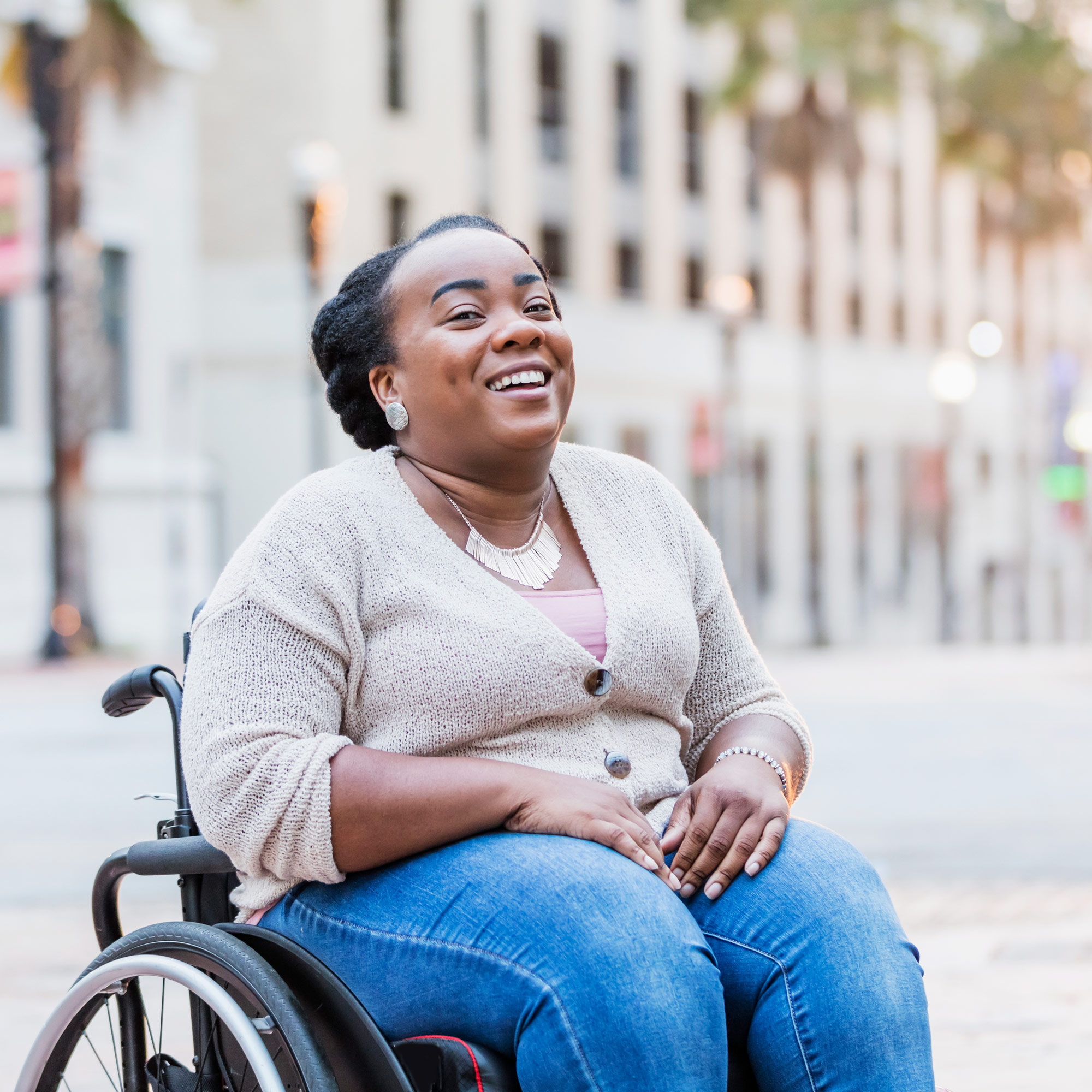 A woman in a wheel chair laughs.