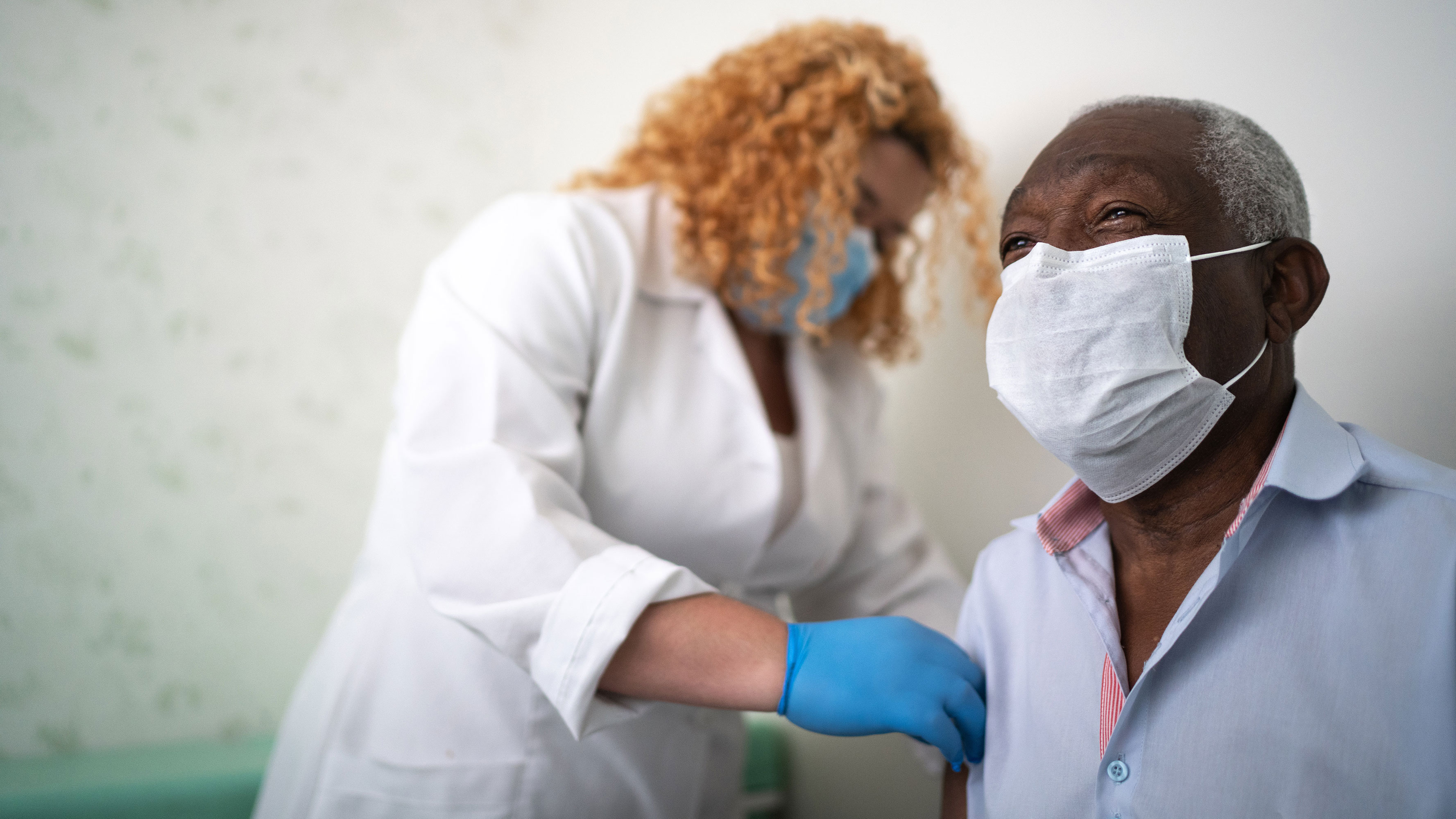 A nurse prepares a patient's arm, both wearing face coverings, for a vaccination