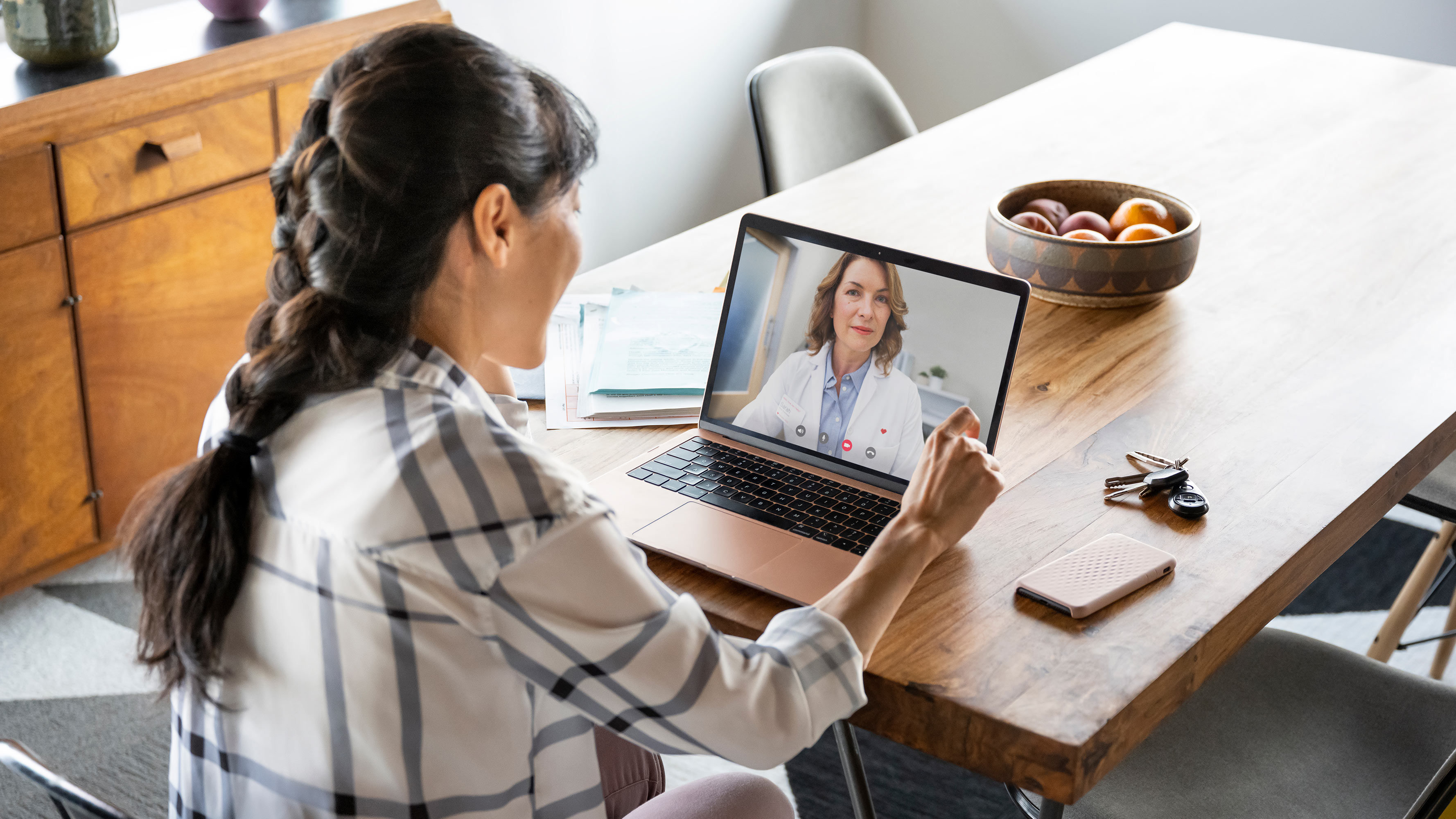 A female patient is seen in her kitchen, conferencing on a video chat with her health care provider.