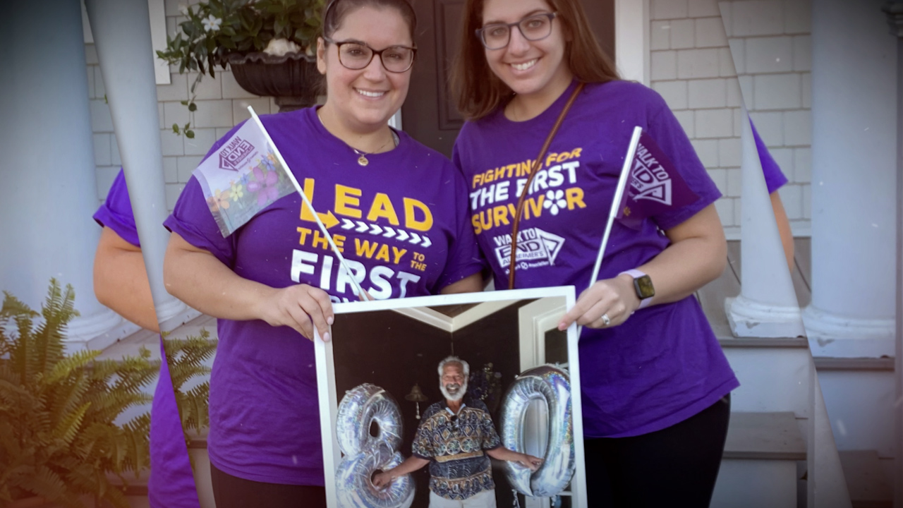 Two women wearing Alzheimer's awareness shirts hold a picture of another individual.