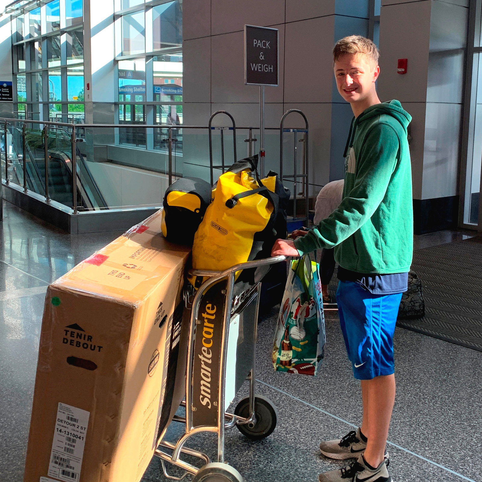 A photo of a teenager at the airport with luggage.