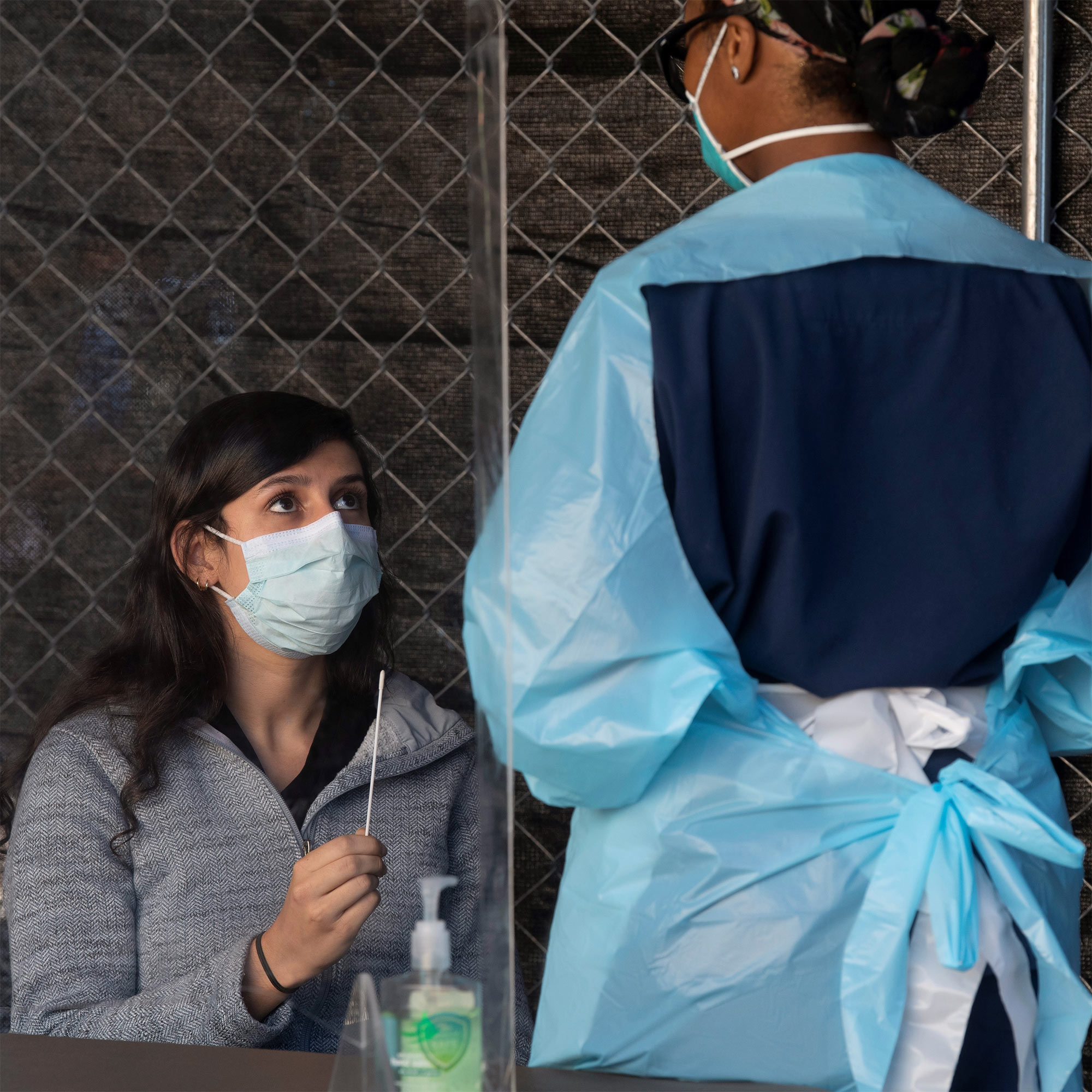 A woman holds a nasal swab as part of a COVID-19 test while a medical professional, (wearing personal protective equipment) advises her on to use the swab to conduct the test.