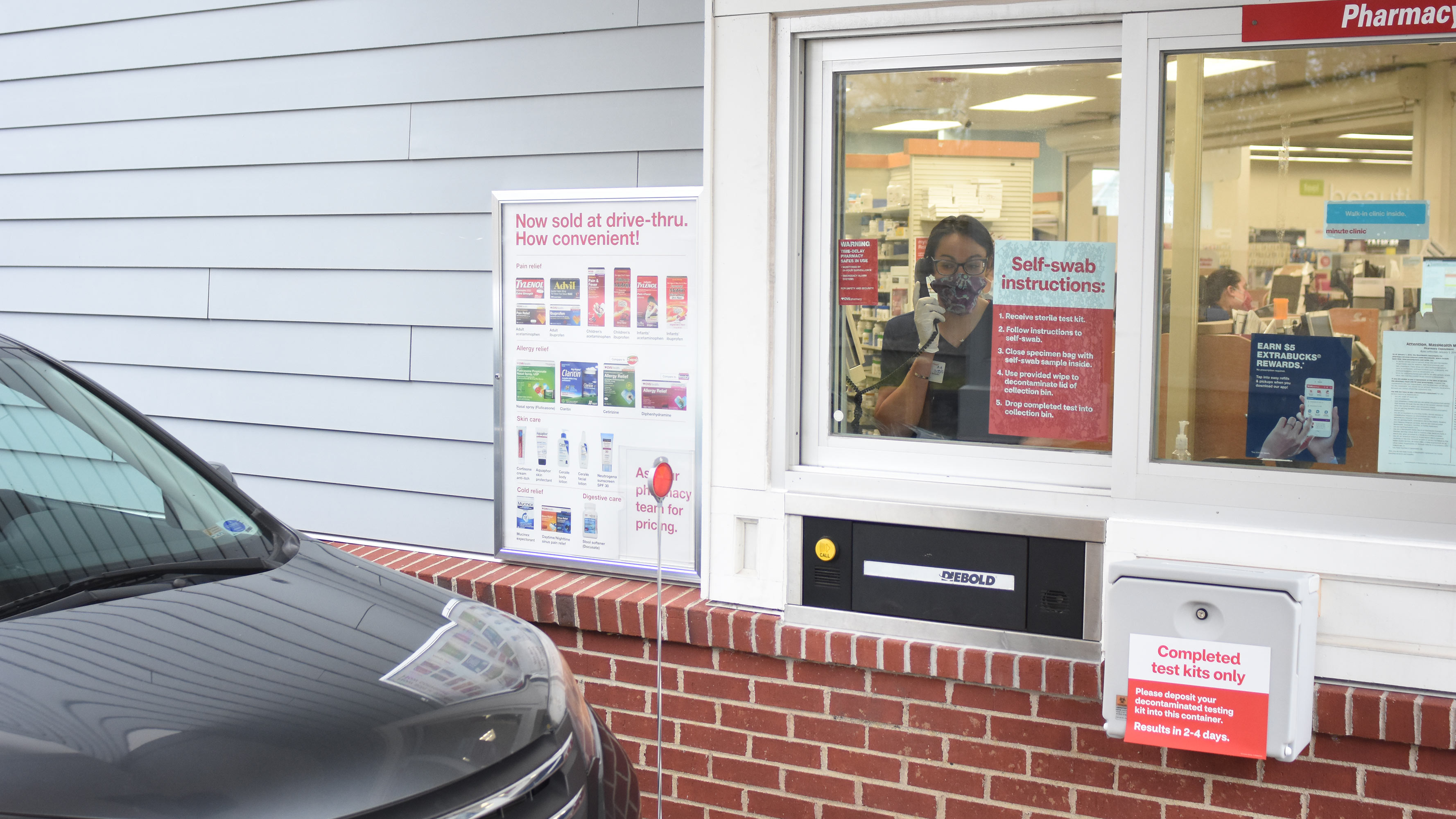 A CVS pharmacists speaks to a customer in the drive-thru at a CVS Pharmacy location.