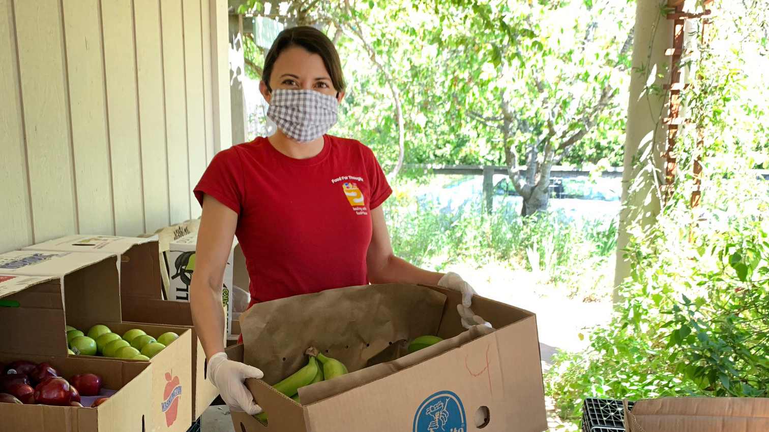 A woman, wearing a face mask and gloves, handles produce in cardboard boxes.