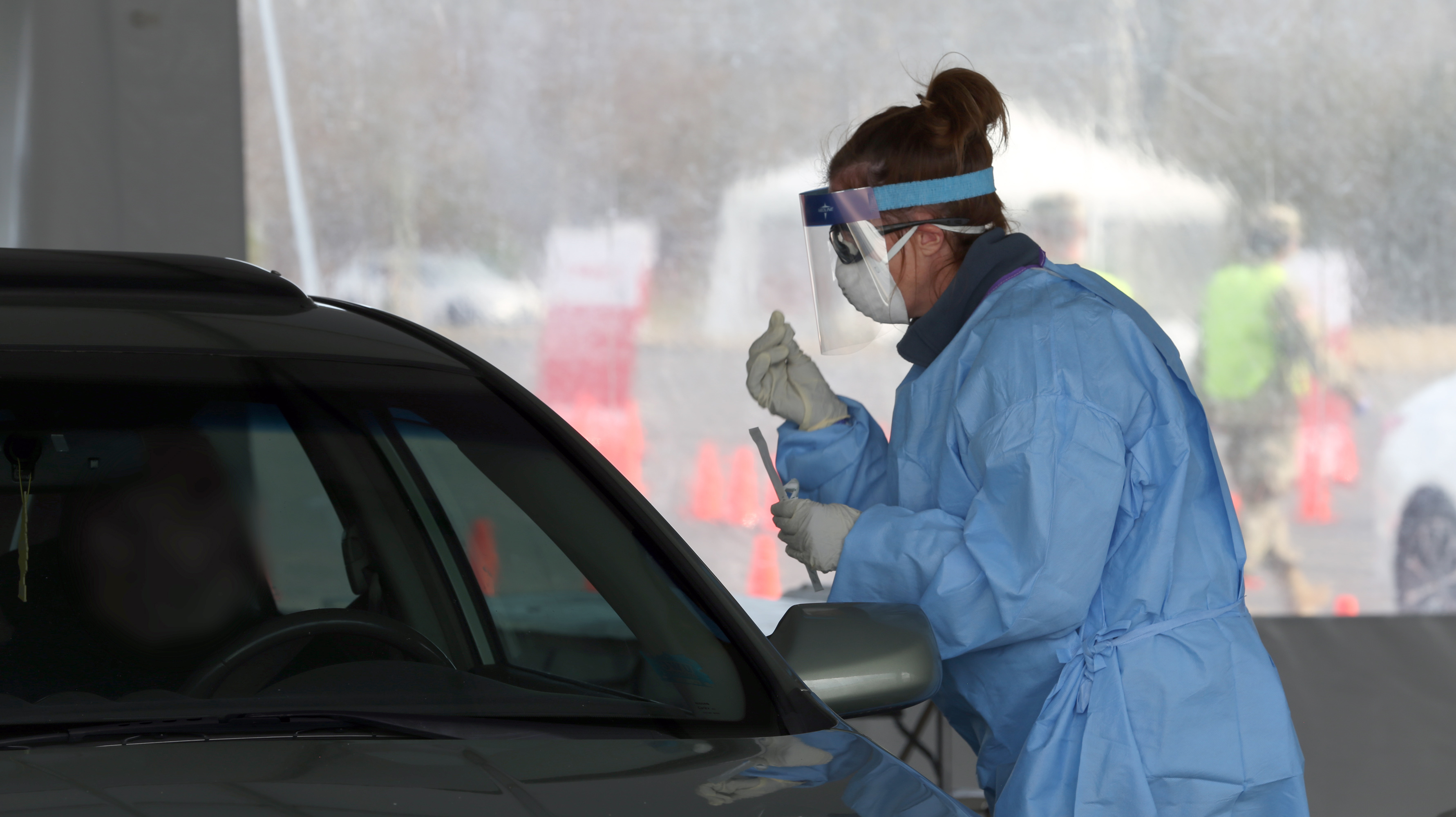 A medical professional examines a swab taken from a patient at a COVID-19 rapid testing drive-through site.