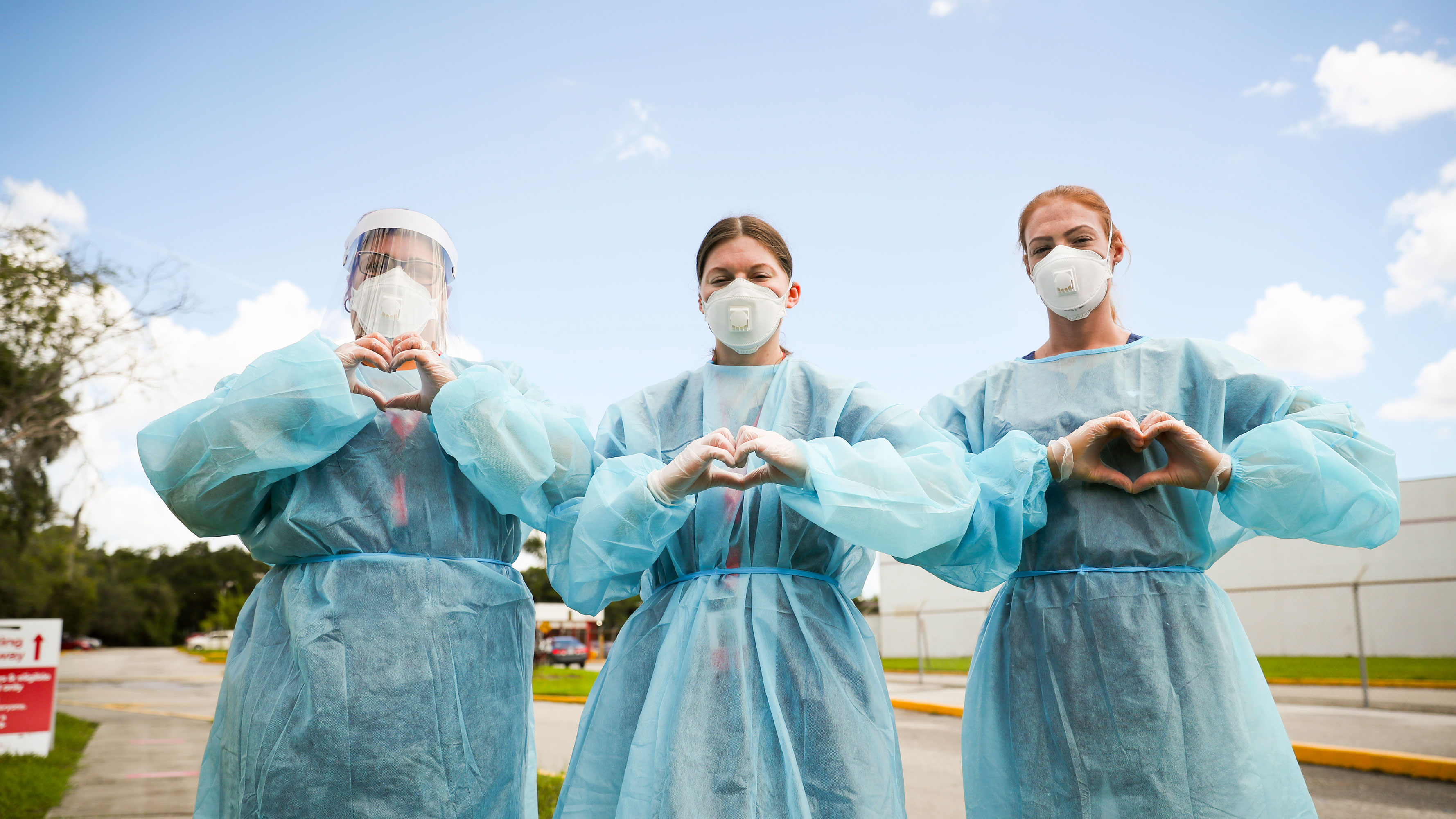 Three health care workers, wearing PPE, make their hands into the shape of hearts.