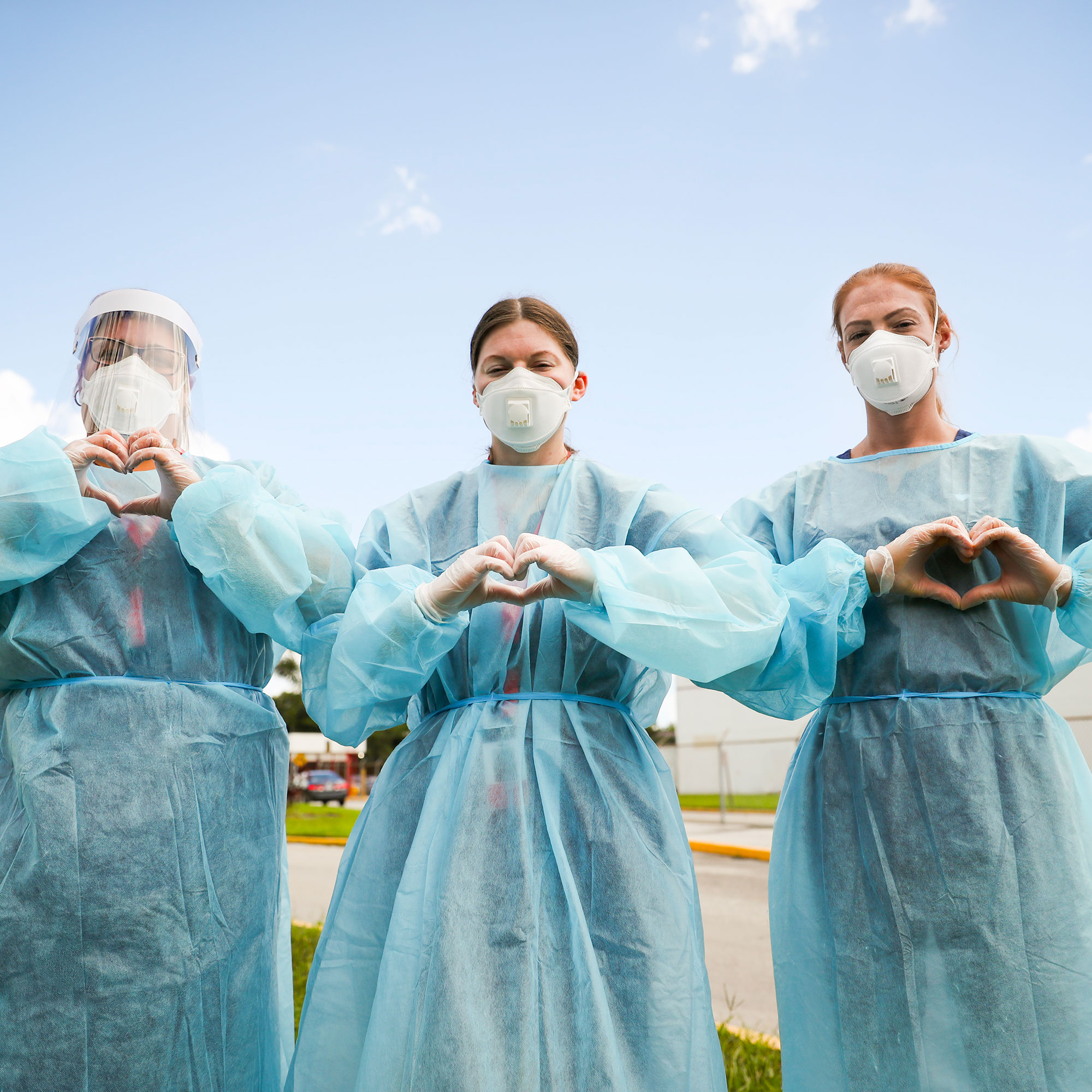 Three health care workers in PPE make their hands into the shape of hearts.
