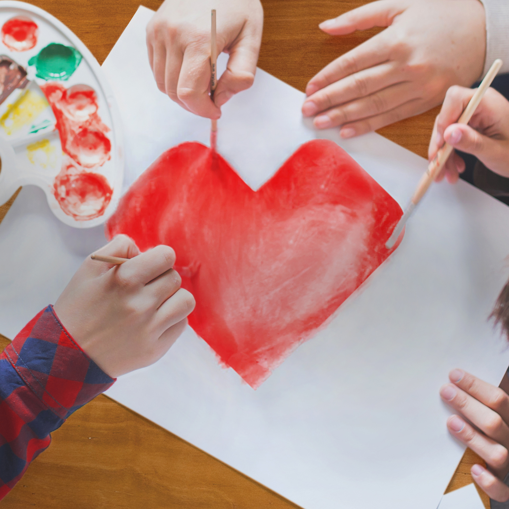 Children painting a red CVS Health heart® on a white canvas using watercolors.