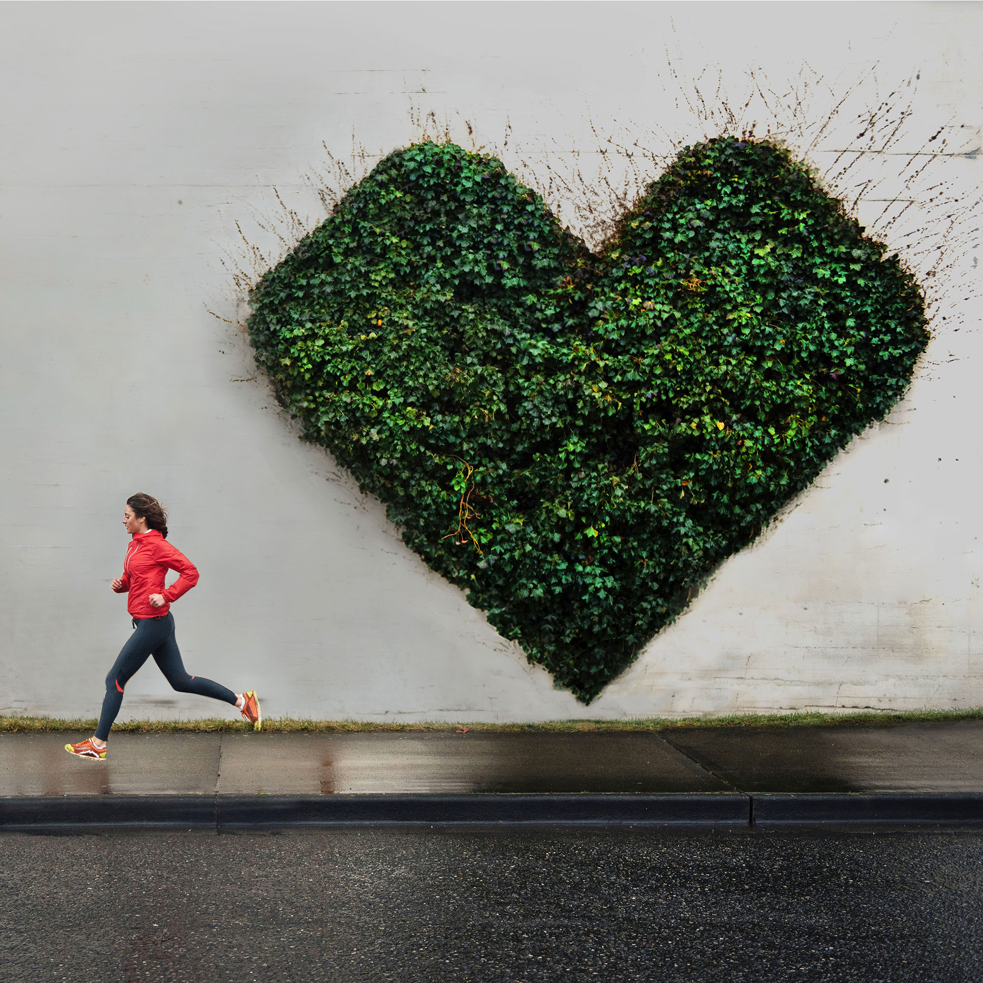 A woman jogs on the sidewalk in the city, passing a stylized CVS Health® heart in the shape of a leafy hedge.