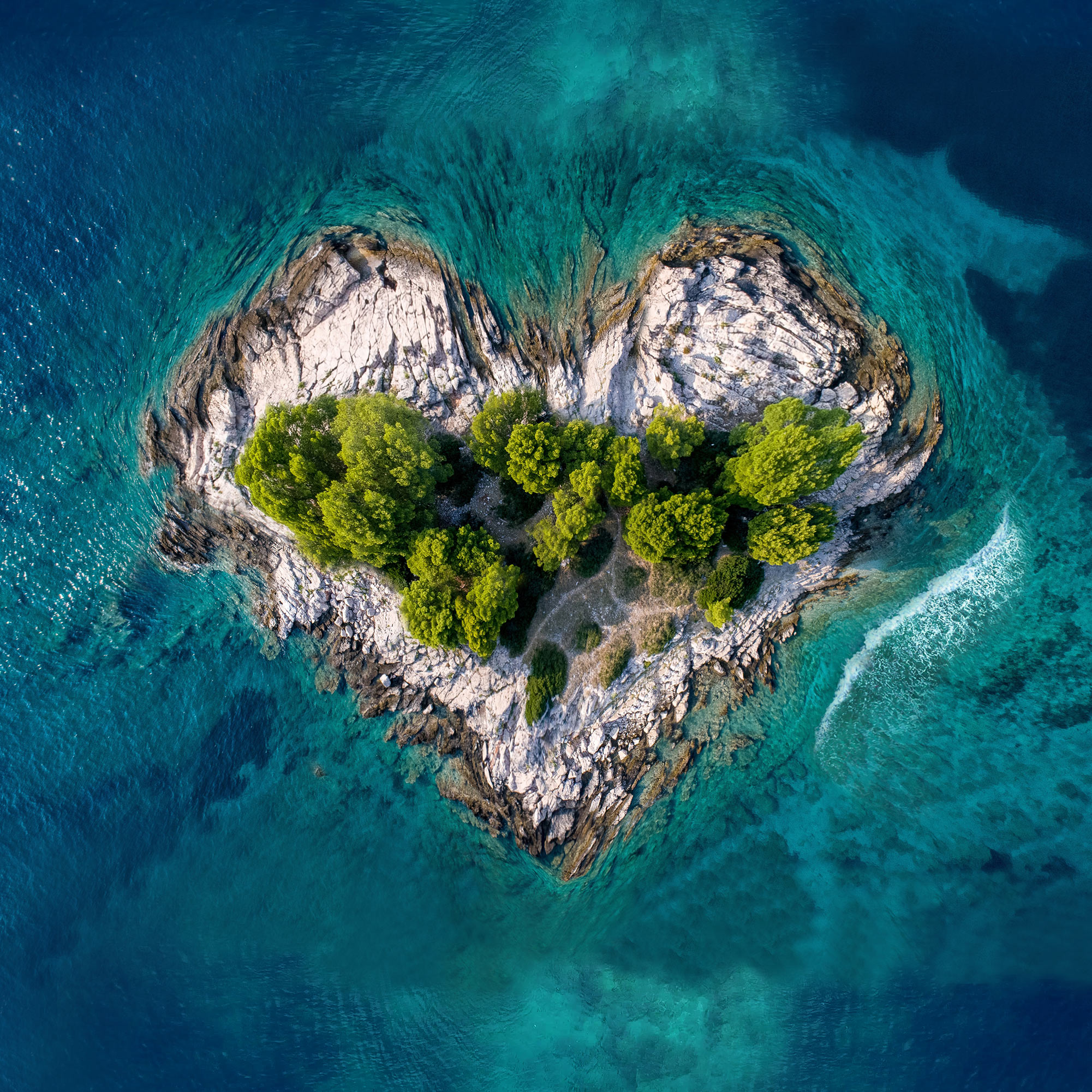 An aerial photo of a tropical island, with bright green trees, among light blue-colored waters, shaped like a CVS Health® heart.