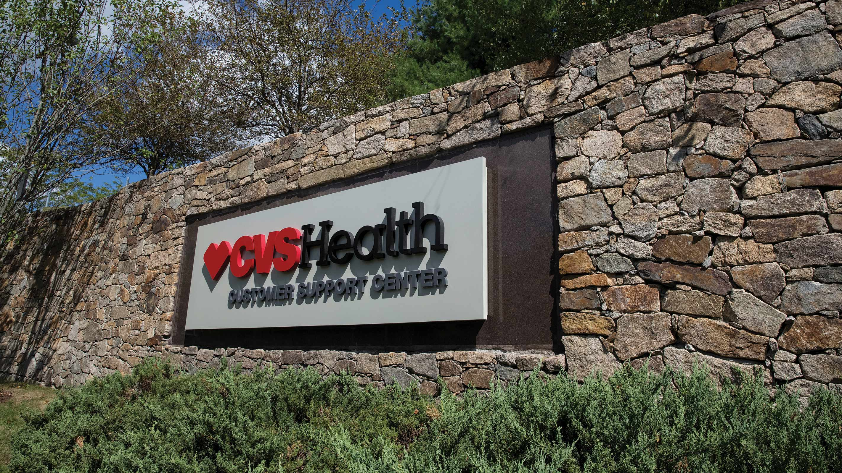 A photo of the exterior sign on the stone wall, outside of the CVS Health Customer Service Center in Woonsocket, Rhode Island.