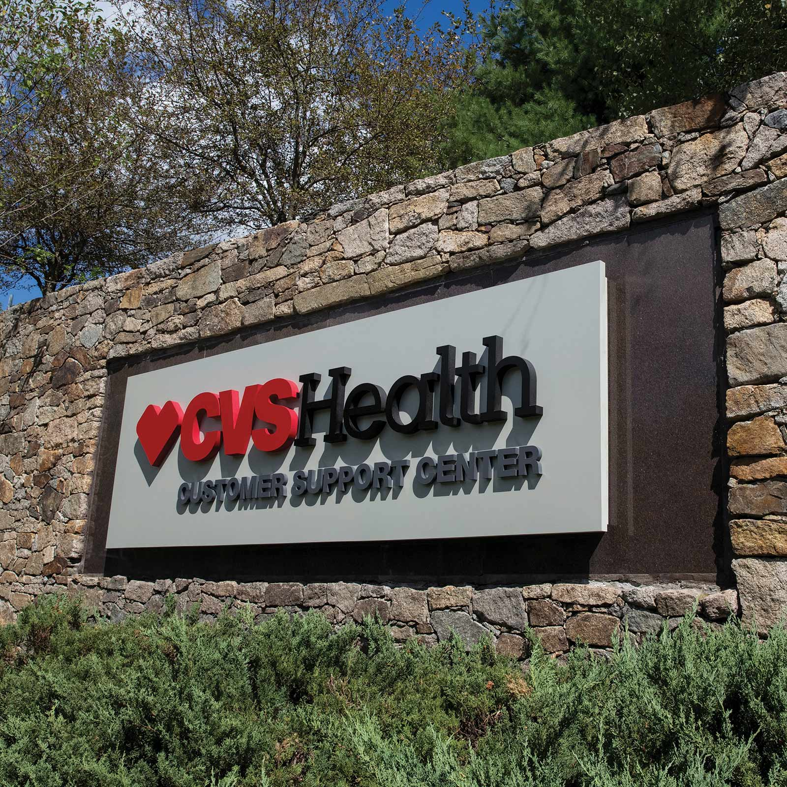 A photo of the exterior sign on the stone wall, outside of the CVS Health Customer Service Center in Woonocket, Rhode Island.