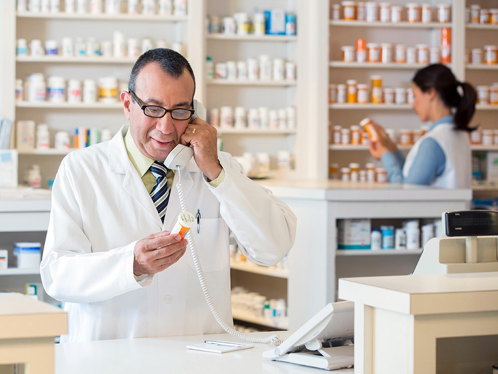 A Hispanic pharmacist fills a prescription.