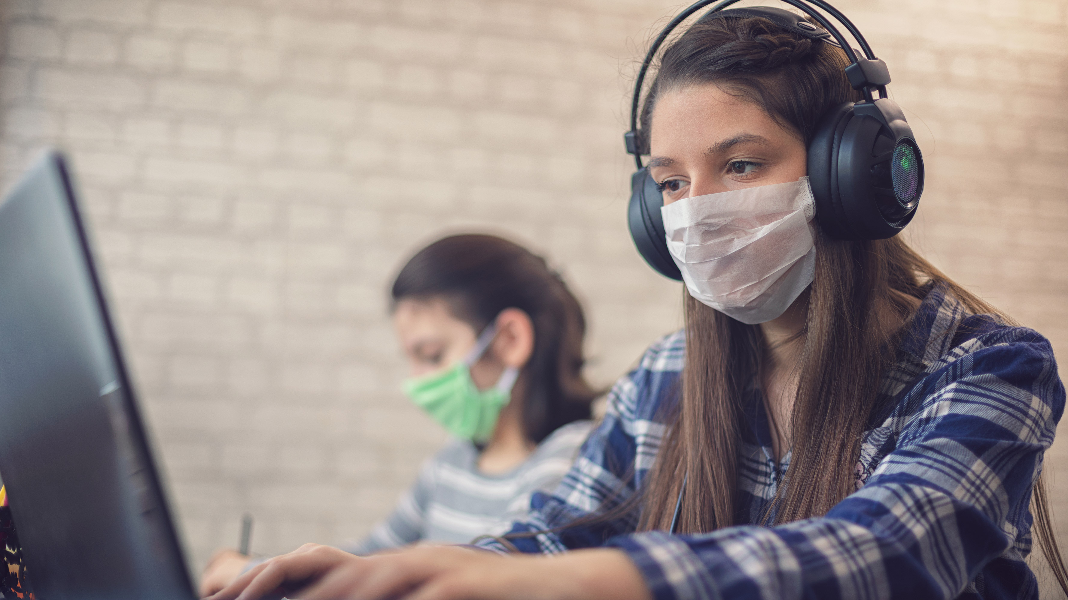 A young female student is seen wearing headphones and a face mask using a computer.