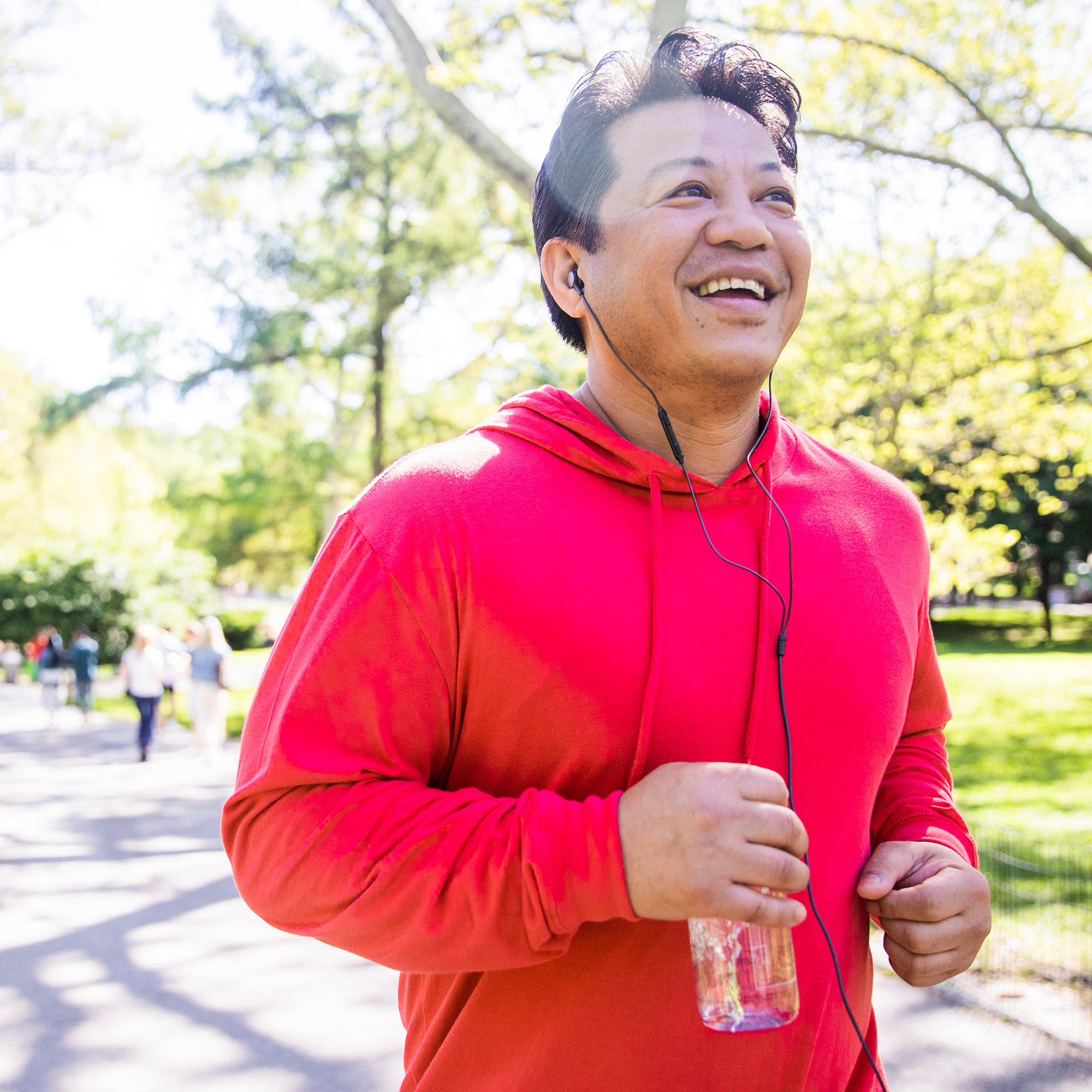 A man wearing a red hooded sweatshirt runs through a park while listening to a podcast on his mobile phone.