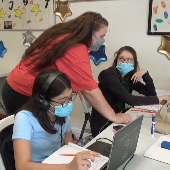 A female educator and a young student, both wearing face masks for protection, helps the student with an assignment in a classroom.