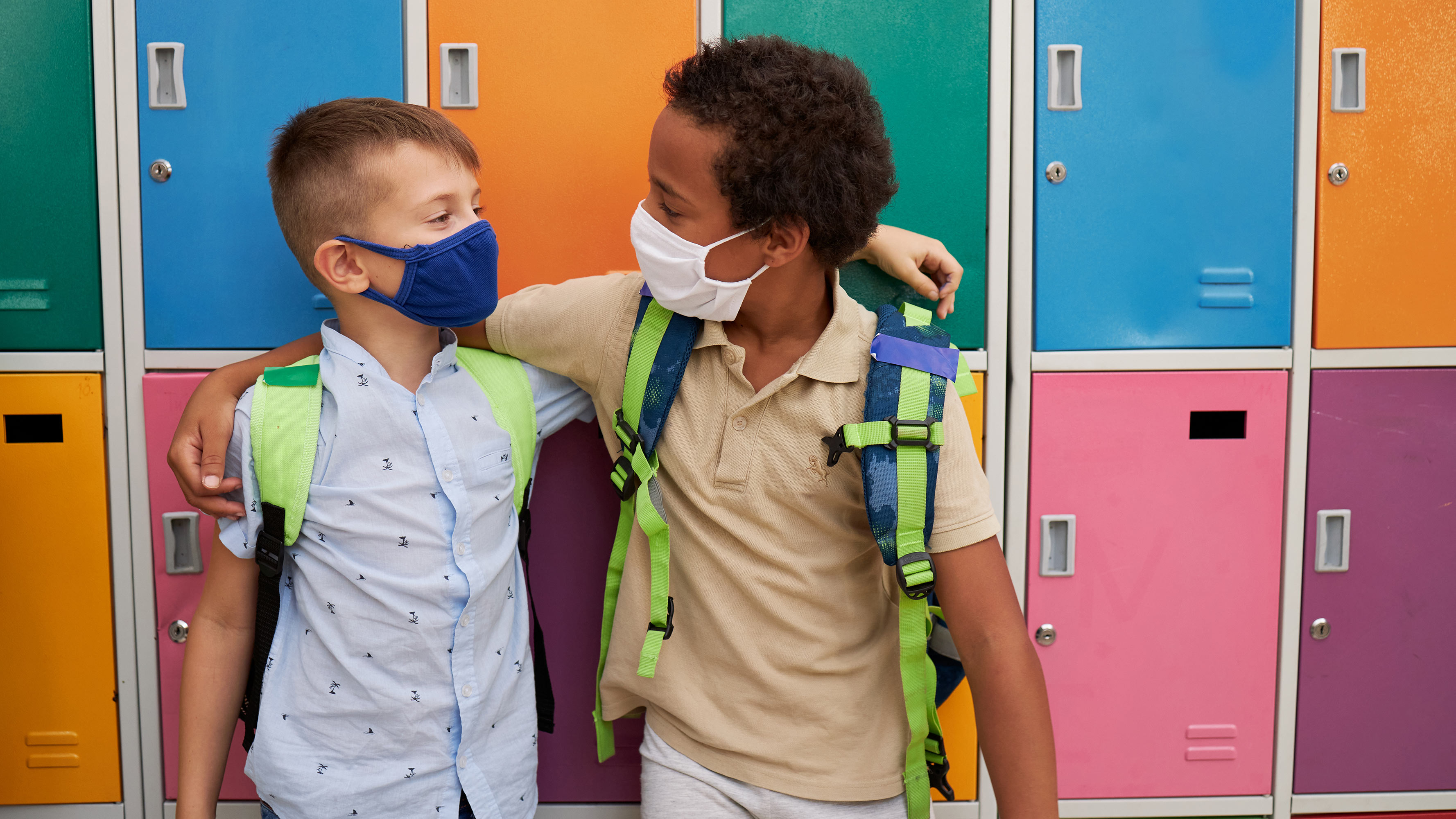 Two young children, wearing face masks and backpacks, hang out in front of bright-colored lockers in an elementary school classroom.