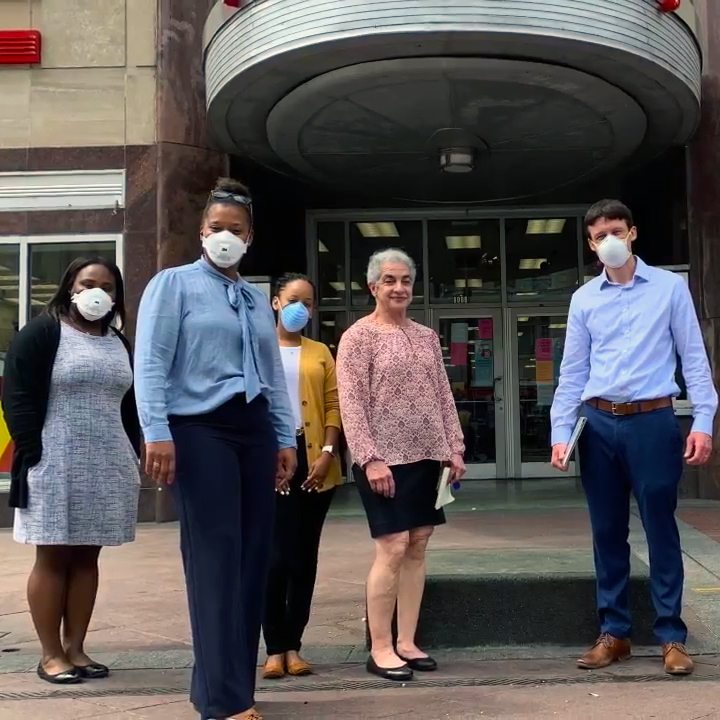 Several employees and volunteers stand outside of the Canal Street CVS Pharmacy wearing masks, prepared to help those affected by COVID-19.