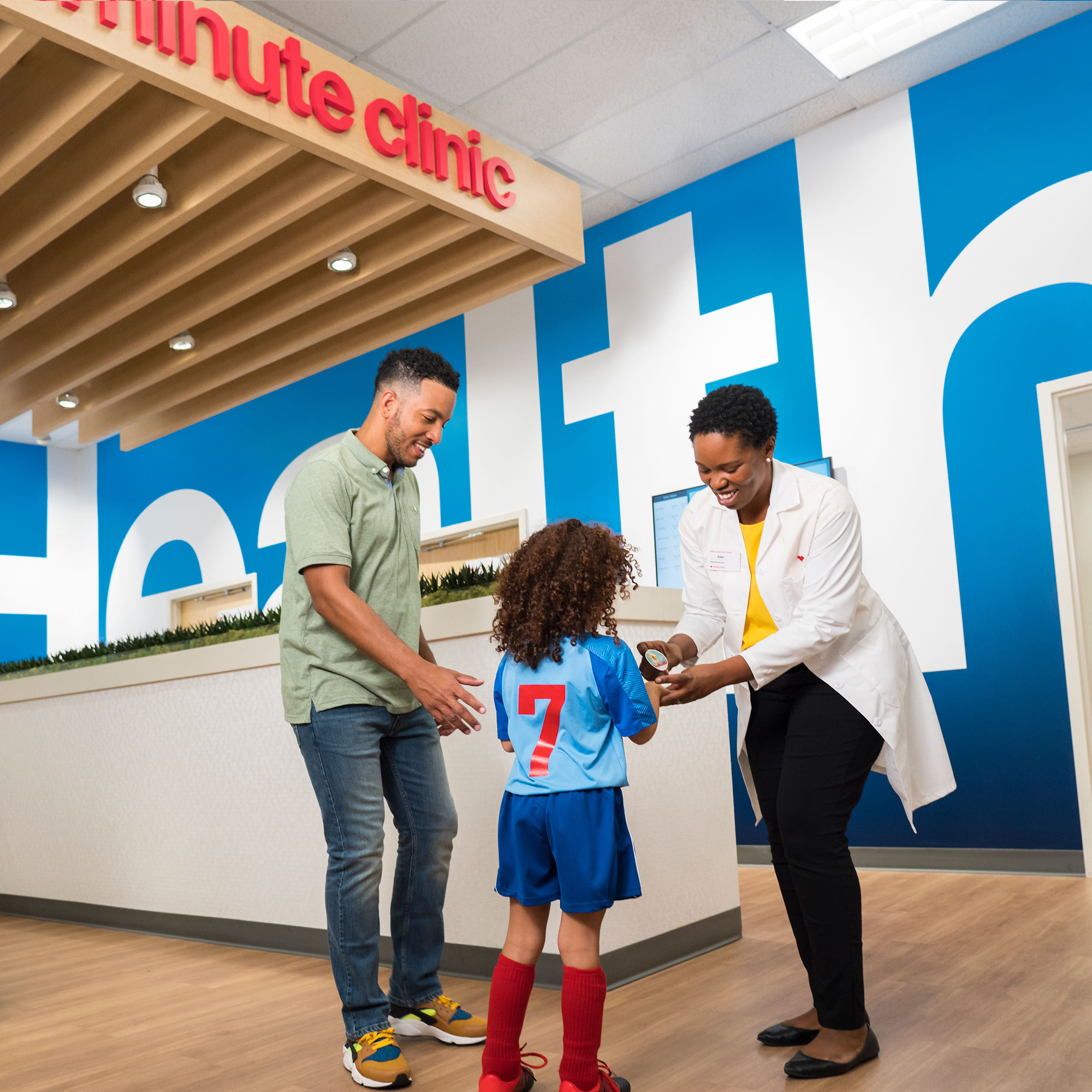A father and daughter talk to a Care Concierge at a HealthHUB.
