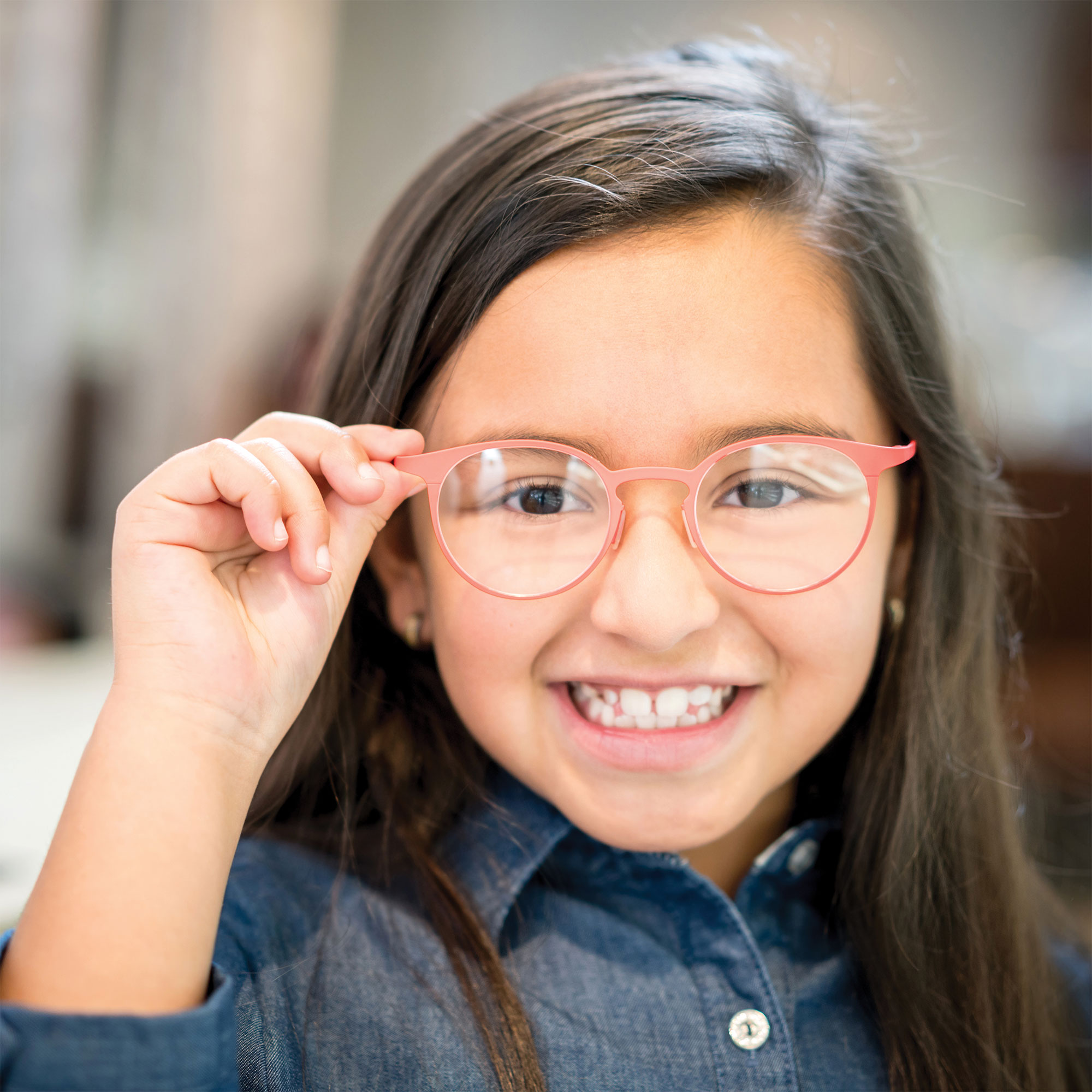 A young girl smiles while holding the frame of her pink horn-rimmed glasses