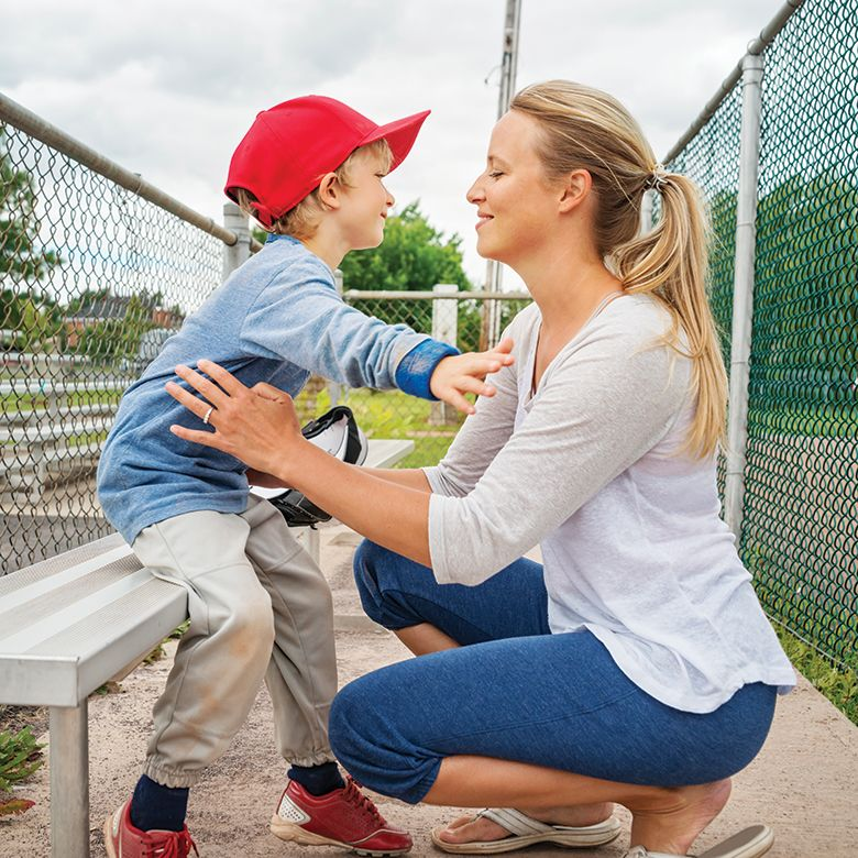 A photo mother supporting her young son at a baseball game, while he sits on a bleacher seat.