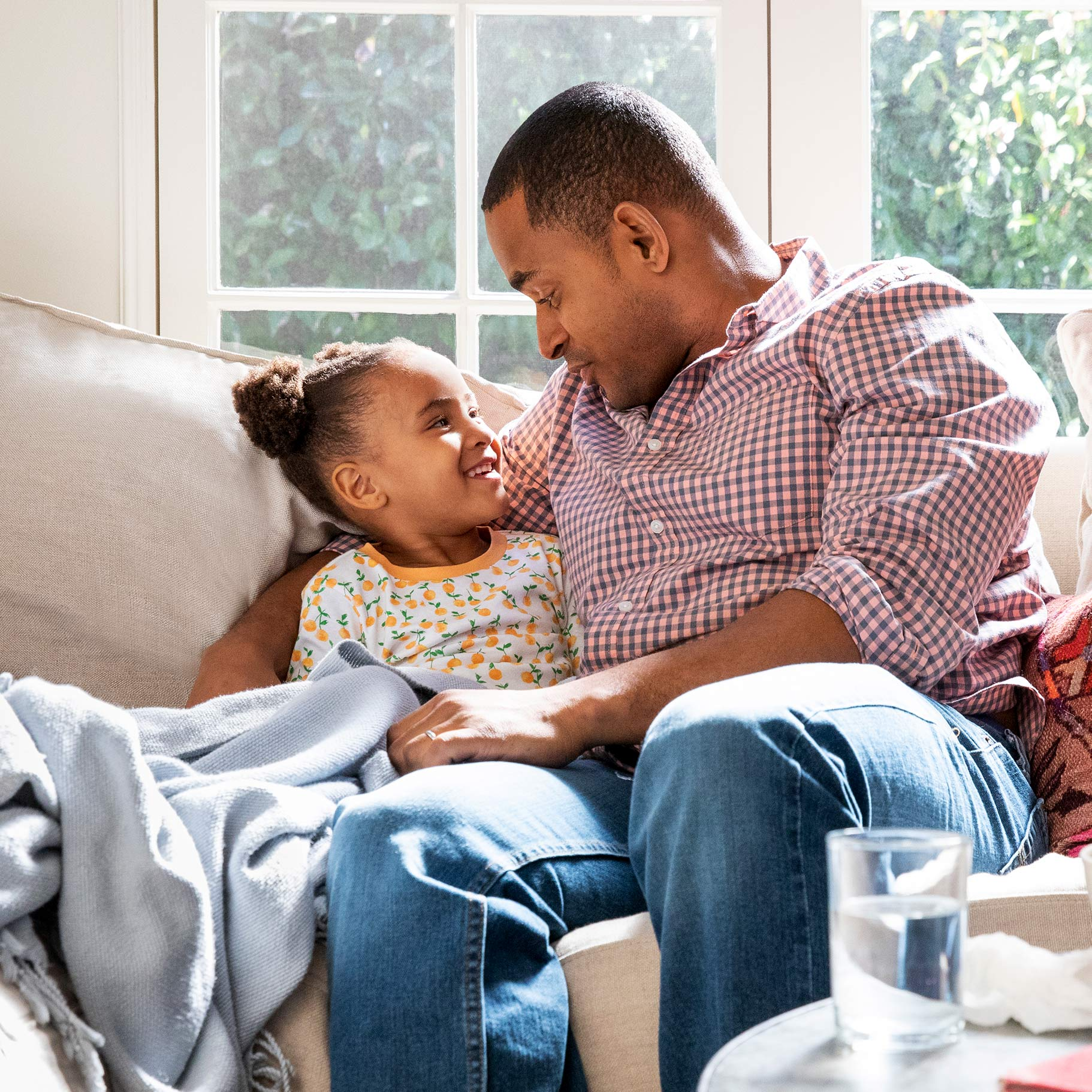 A father and daughter sit on a sofa in their brightly-lit living room, with a CVS Pharmacy delivery box seen in the foreground containing an assortment of products.