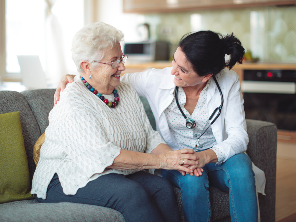 A patient and a caregiver sitting on a sofa.