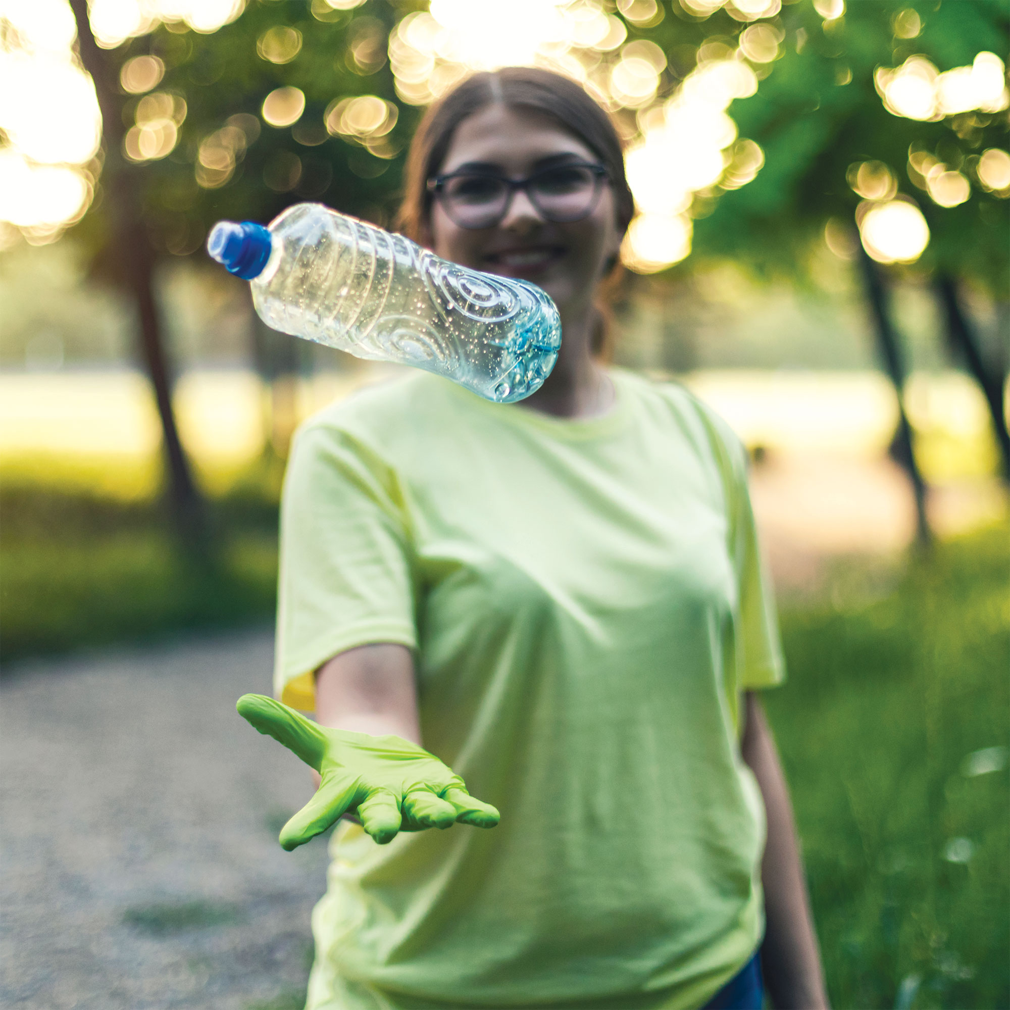 A teenager wears gloves to pick up plastic waste in a park.