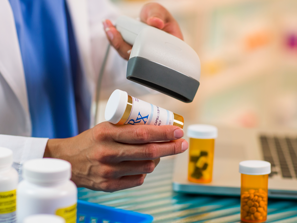 Pharmacist scanning pill bottle.